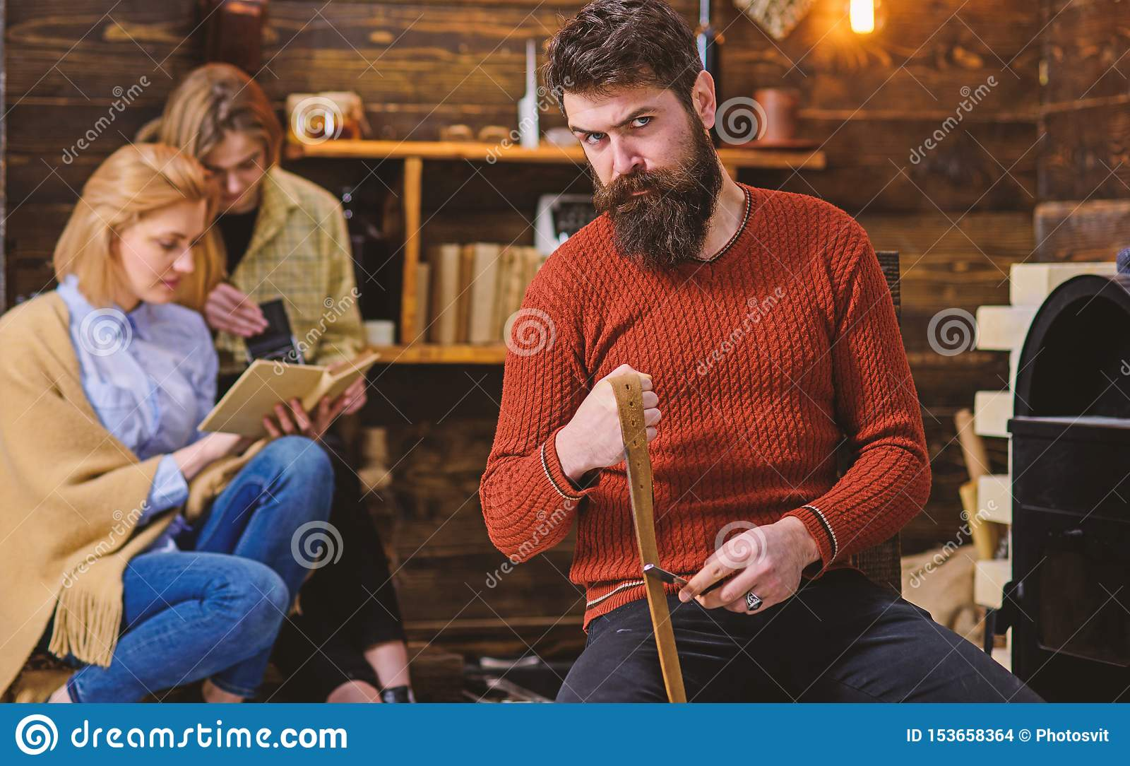 Boscaiolo con lo sguardo rigoroso e la barba folta lunga che tentano rasoio o coltello, concetto del pericolo Uomo barbuto in ret