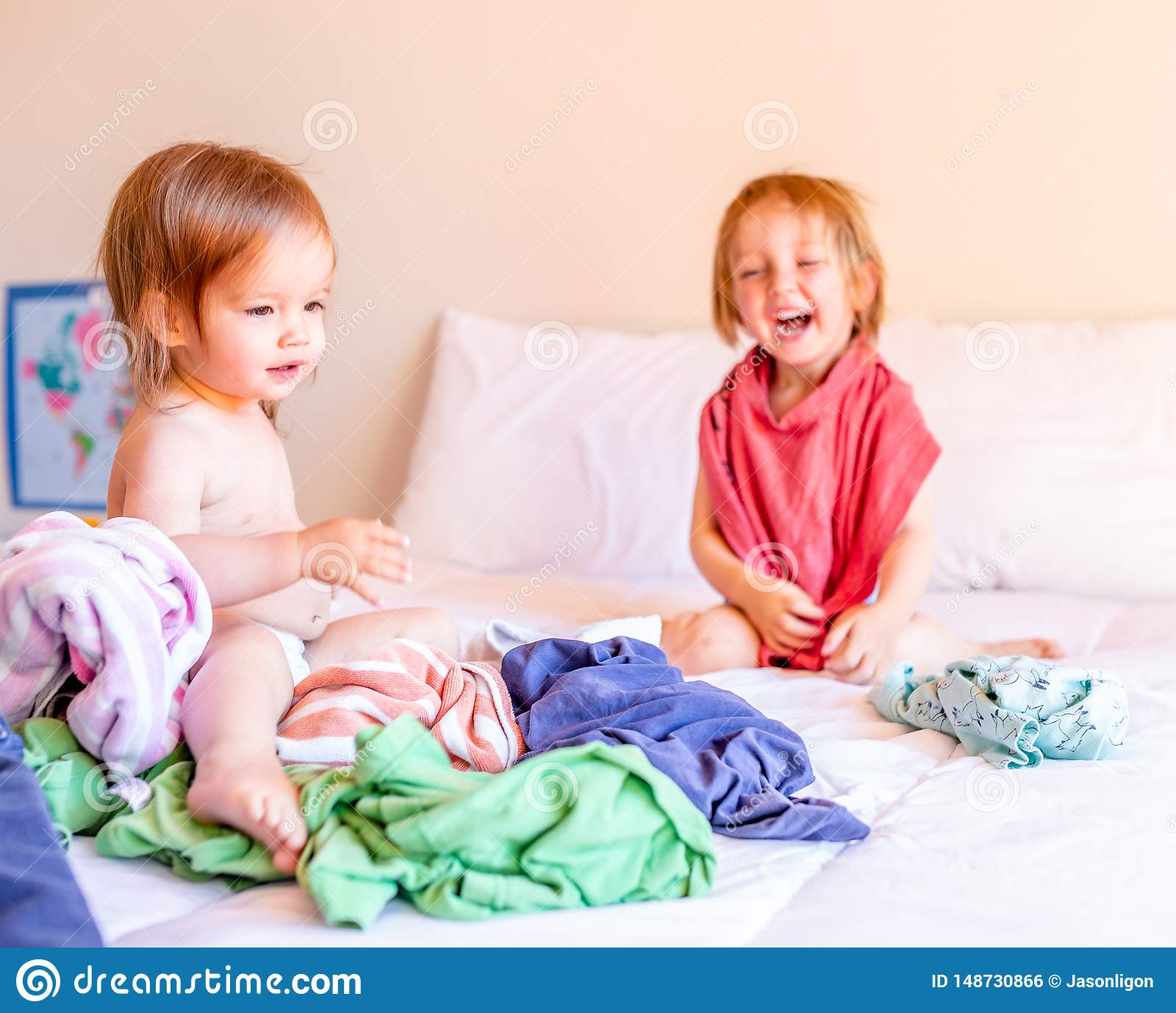 Boshafter Bruder und Schwester Play in einem Stapel der W?scherei auf dem Bett Aufbau mit Schrauben und Muttern