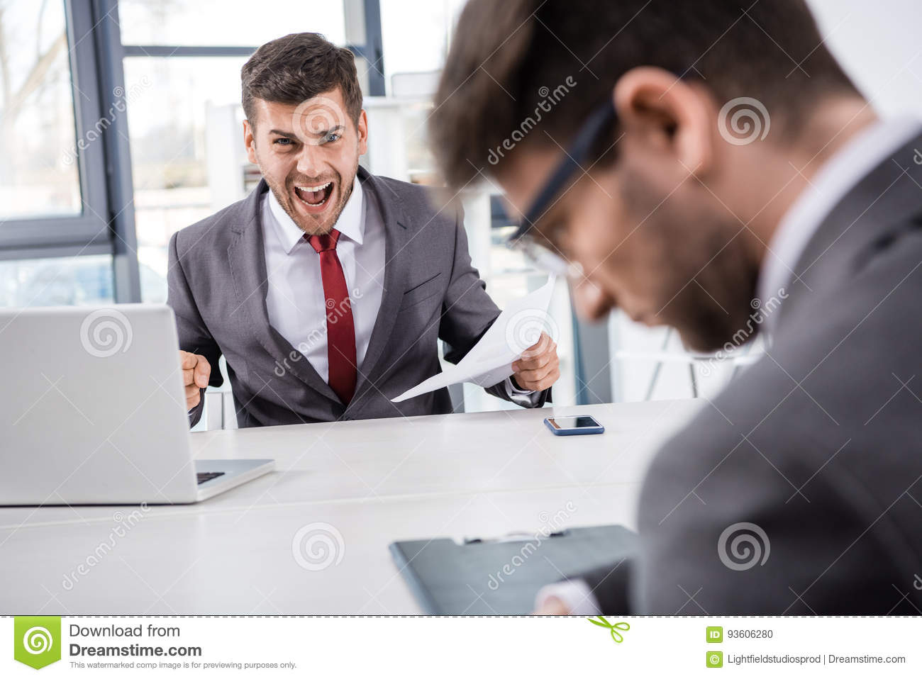 Boss with documents shouting at upset colleague at workplace