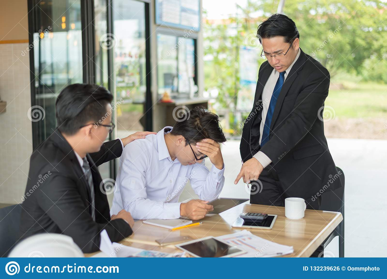Boss shouted to employee and point his finger to reports, he very angry for Reported sales decrease.