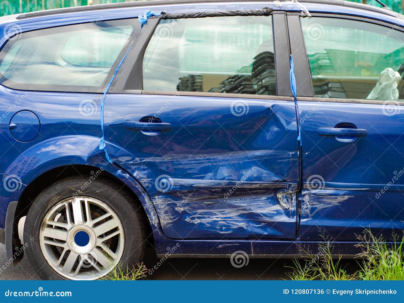 Bosselure bleue de voiture dans une porte