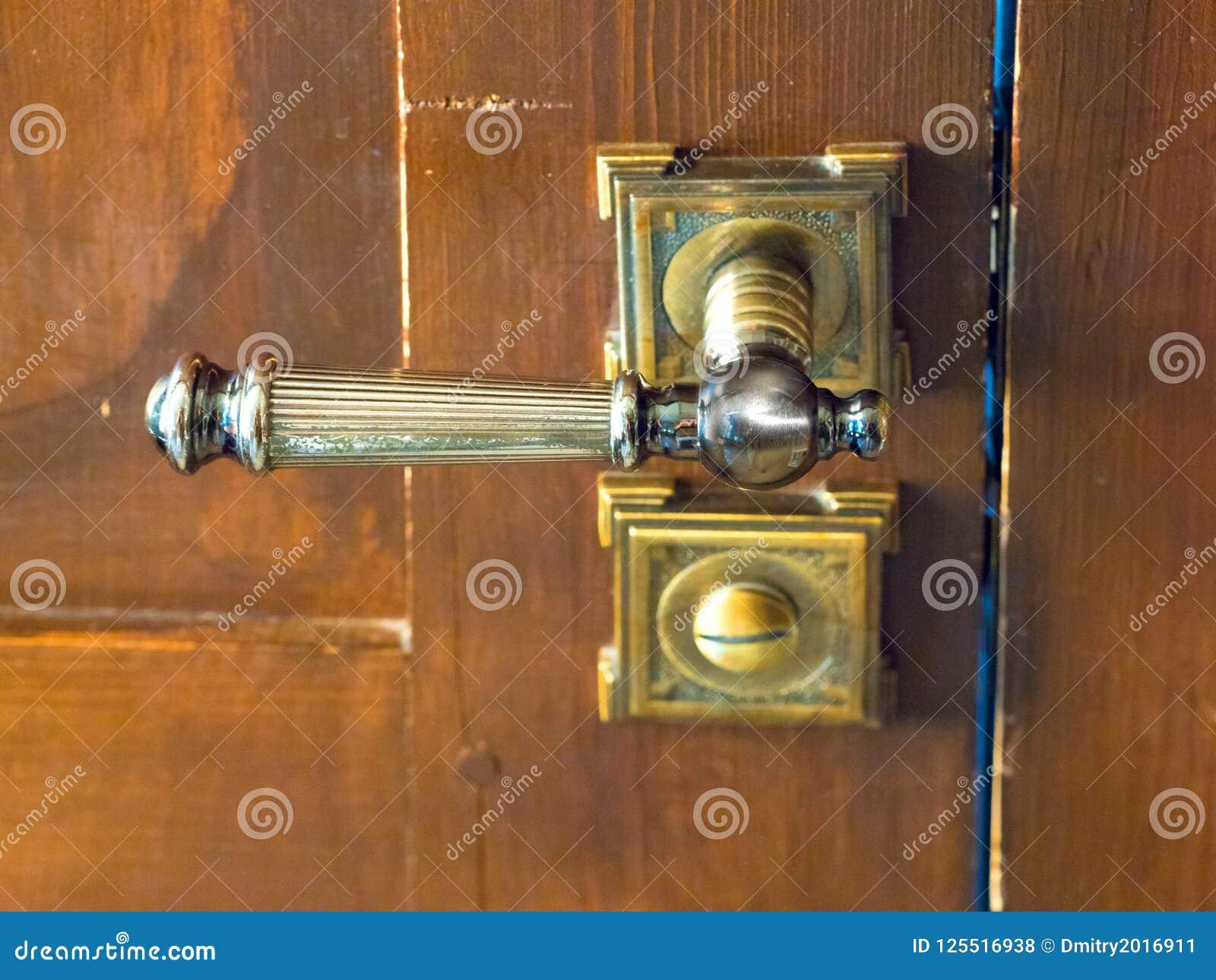Botão de porta velho na porta de madeira