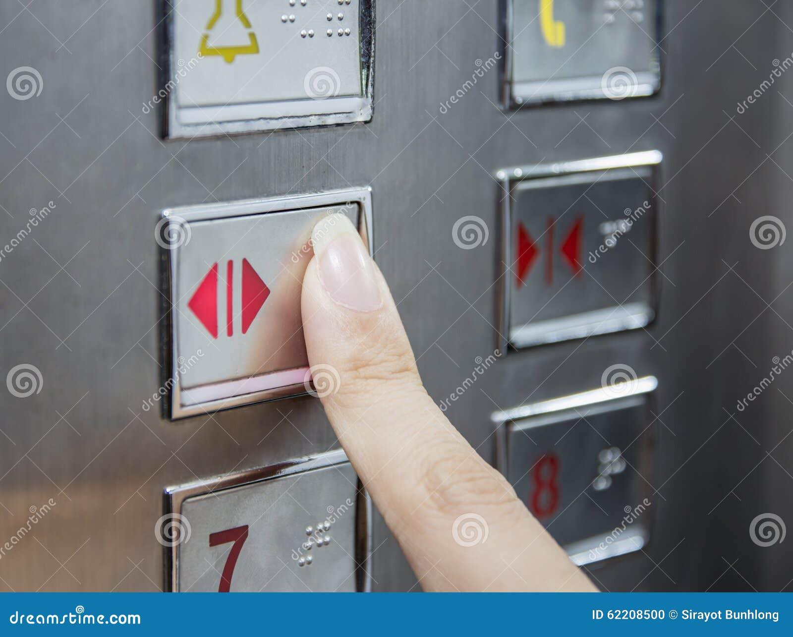 Botão do estar aberto da imprensa da mão no elevador