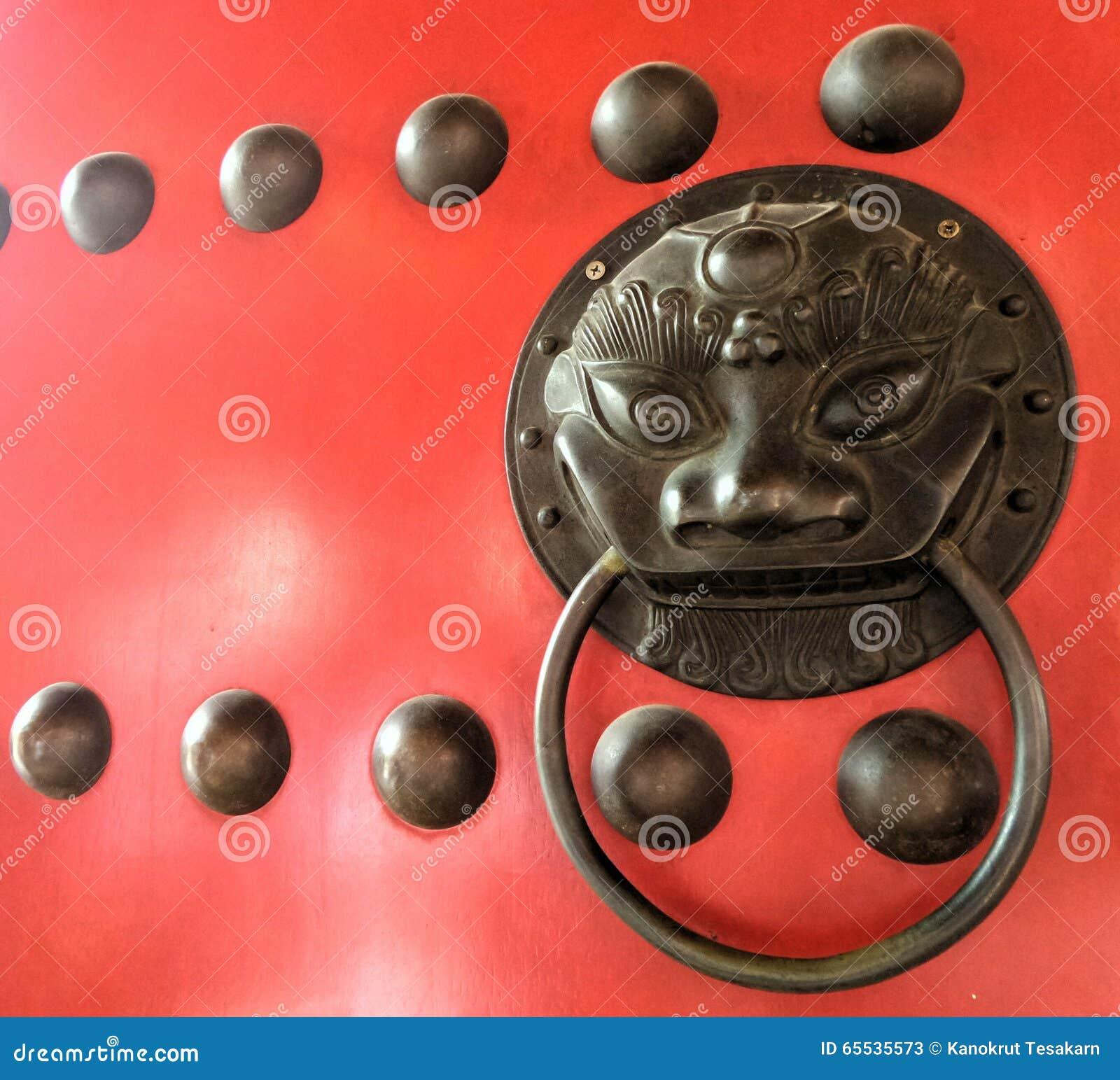 Botón chino del león del bronz en puertas rojas de la puerta