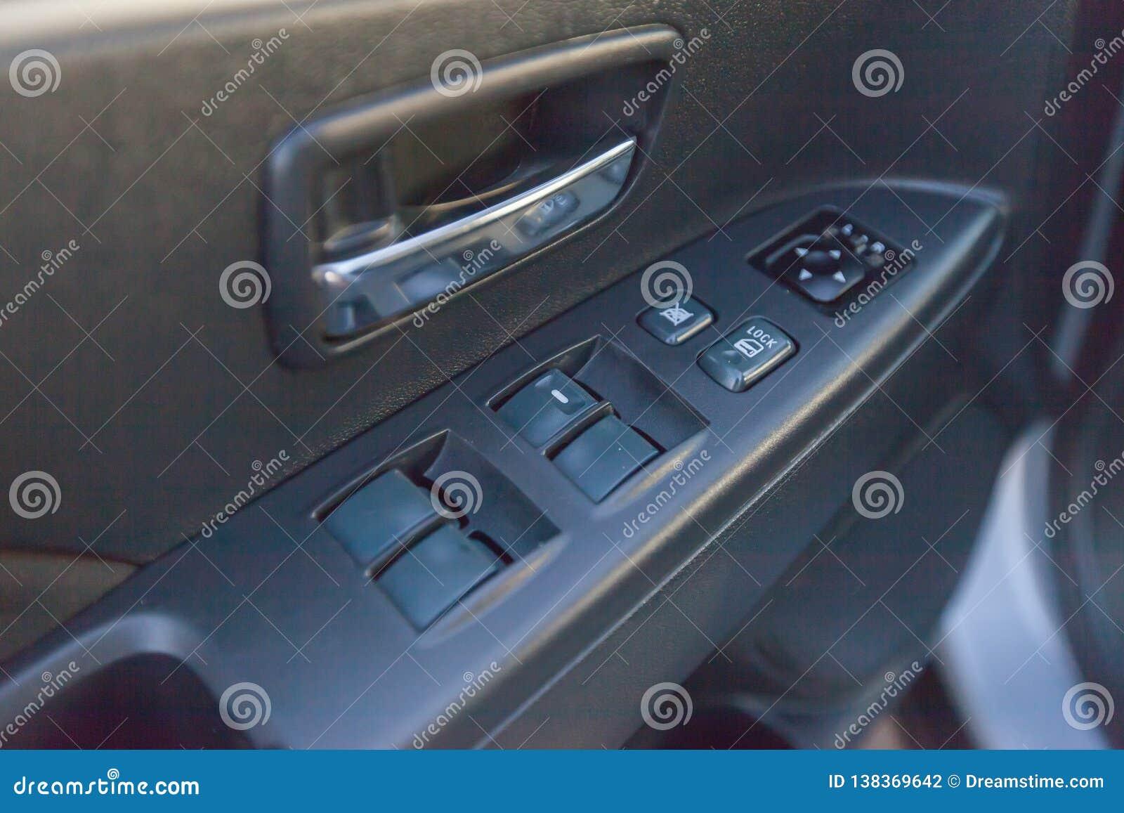Botões de reguladores da janela em uma porta do automóvel