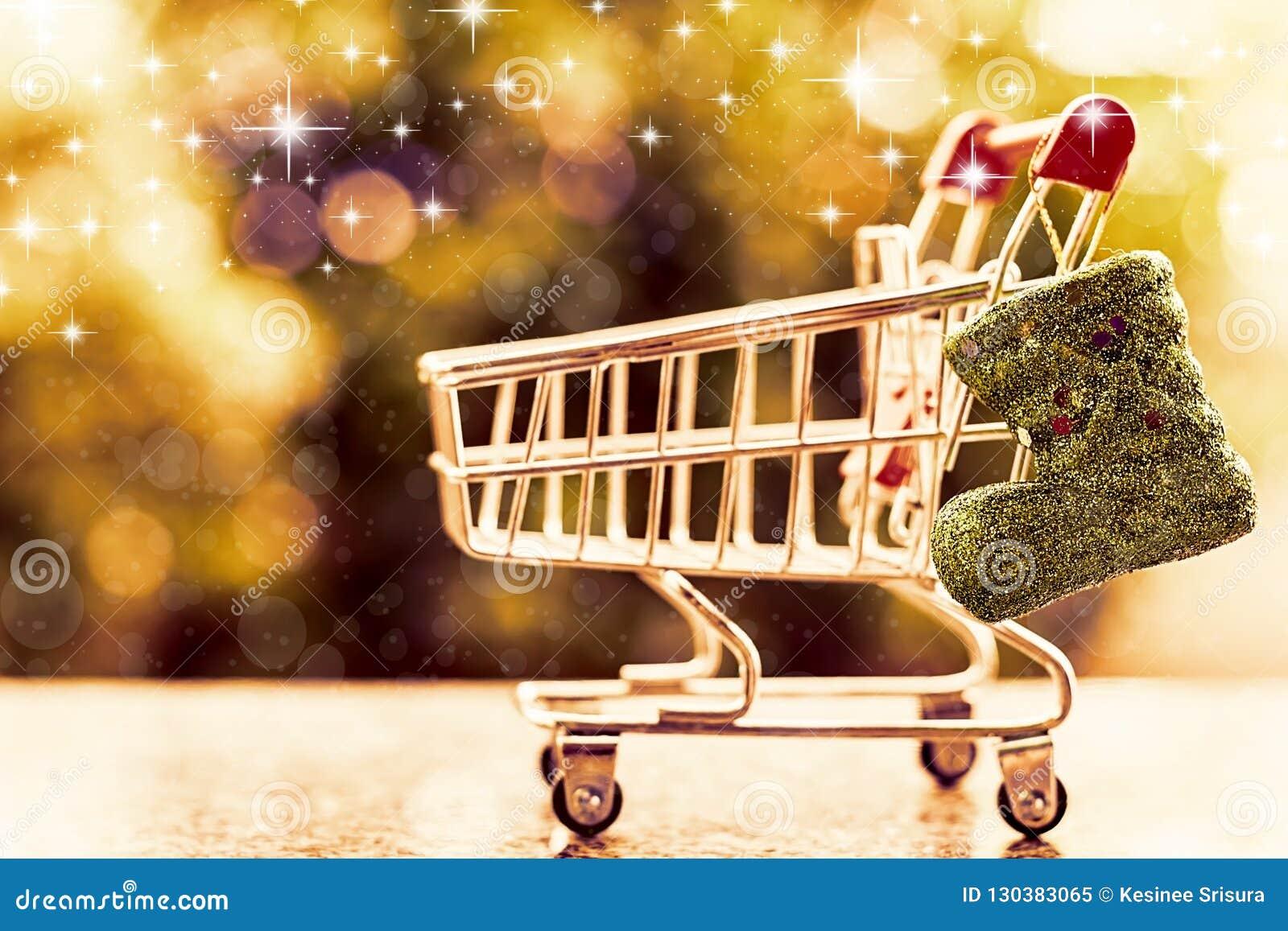 Bota del brillo de Navidad con el mini carro de la compra o carretilla contra azul