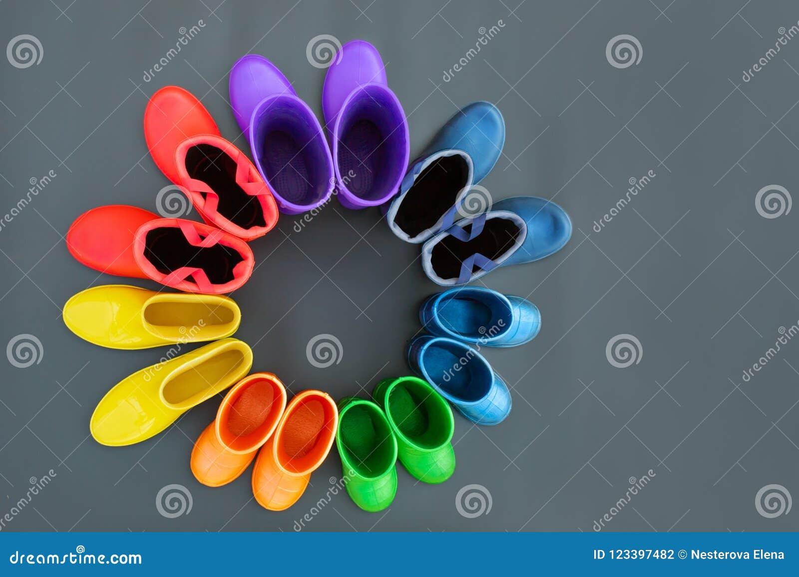 7be886bd8b Botas de borracha coloridas de todas as cores do suporte  arco-íris-vermelho, alaranjado, amarelo, verde, azul, ciano e roxo na  superfície cinzenta em um ...