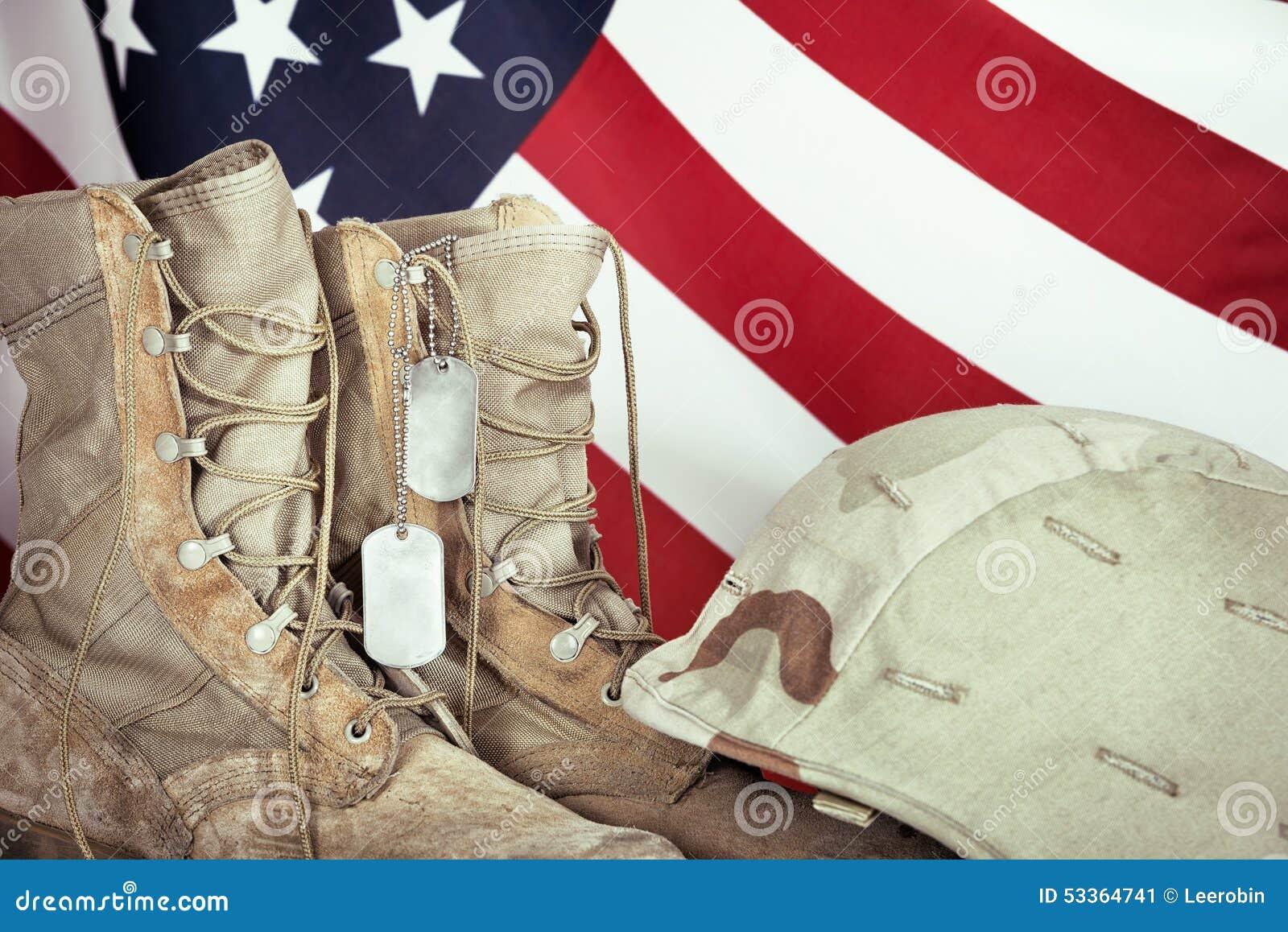 Botas de combate, etiquetas de cão, e capacete velhos com bandeira americana
