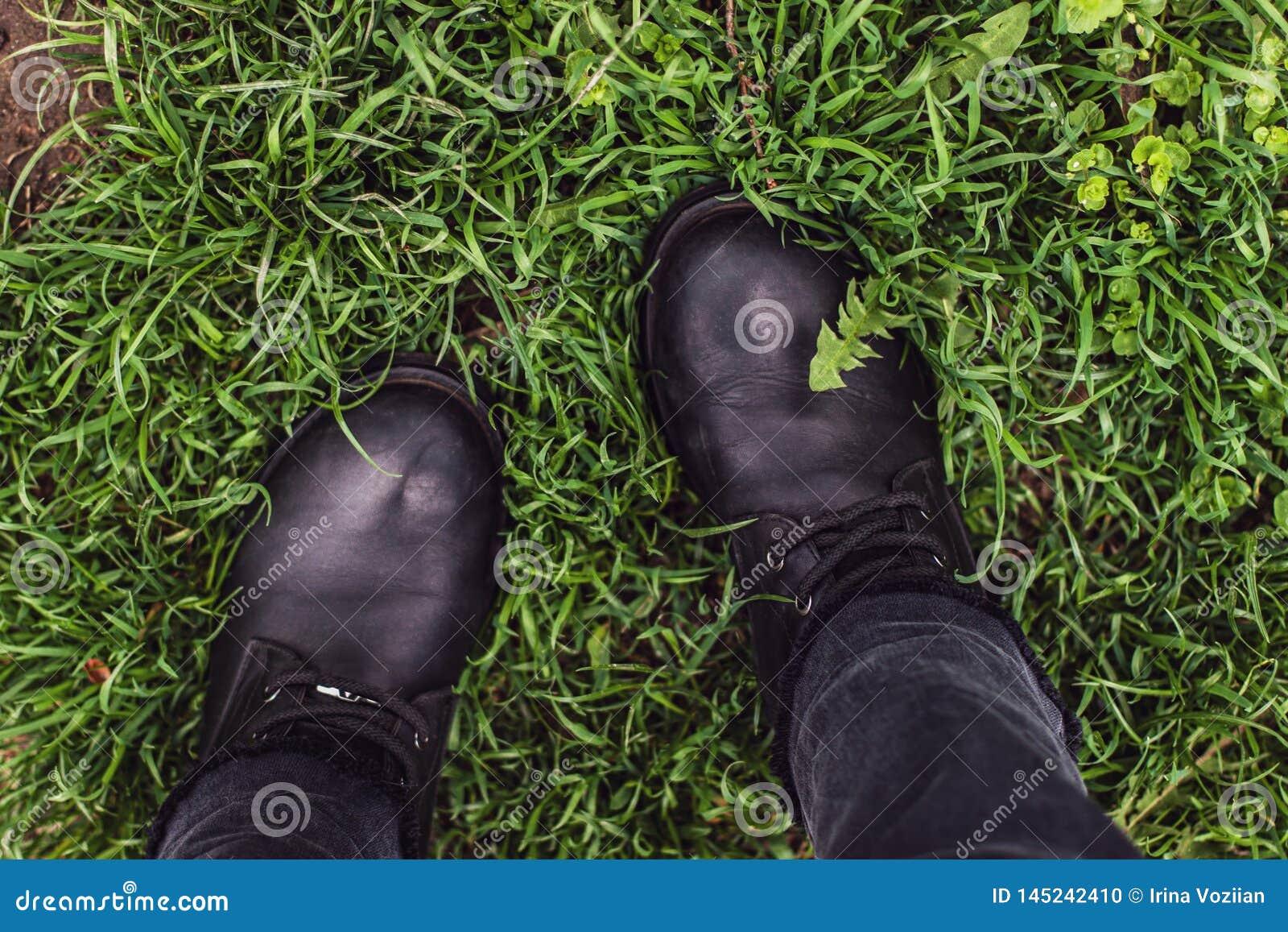 Botas de la mujer negra en hierba verde