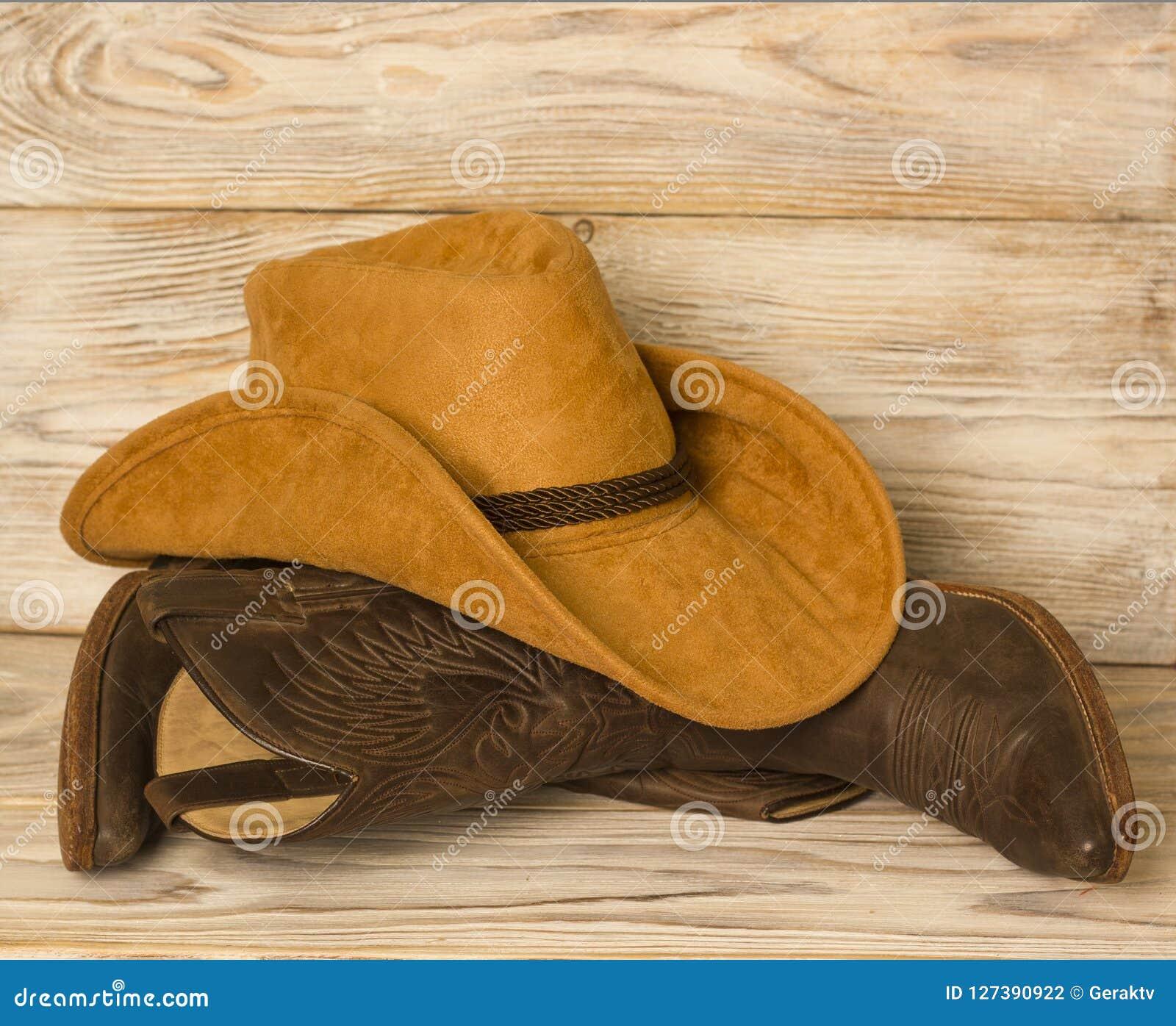 Botas e chapéu ocidentais americanos de vaqueiro no fundo de madeira da textura
