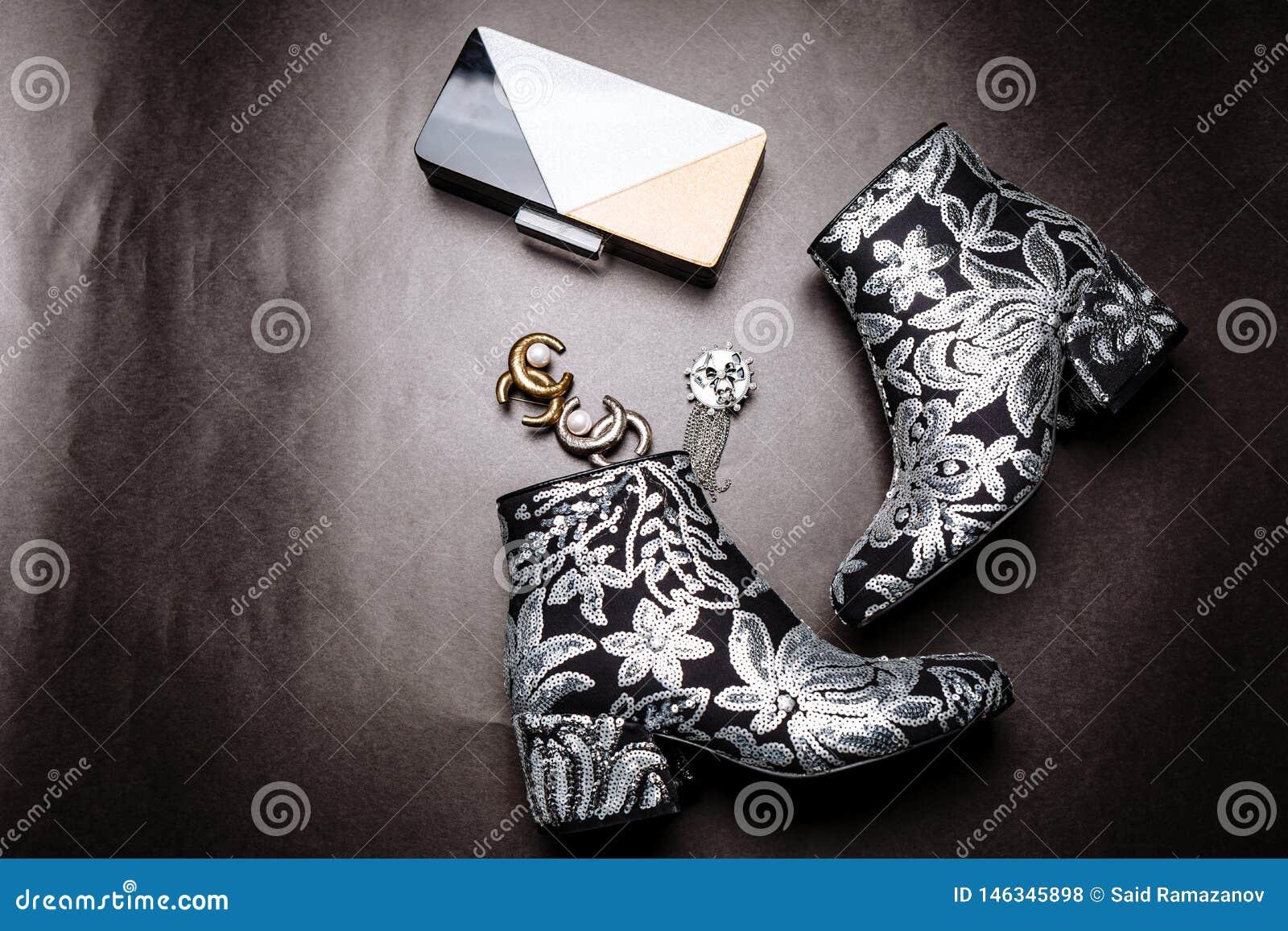 Botas pretas do tornozelo com os saltos grossos decorados com as flores bordadas com lantejoulas de prata e uma embreagem e broch