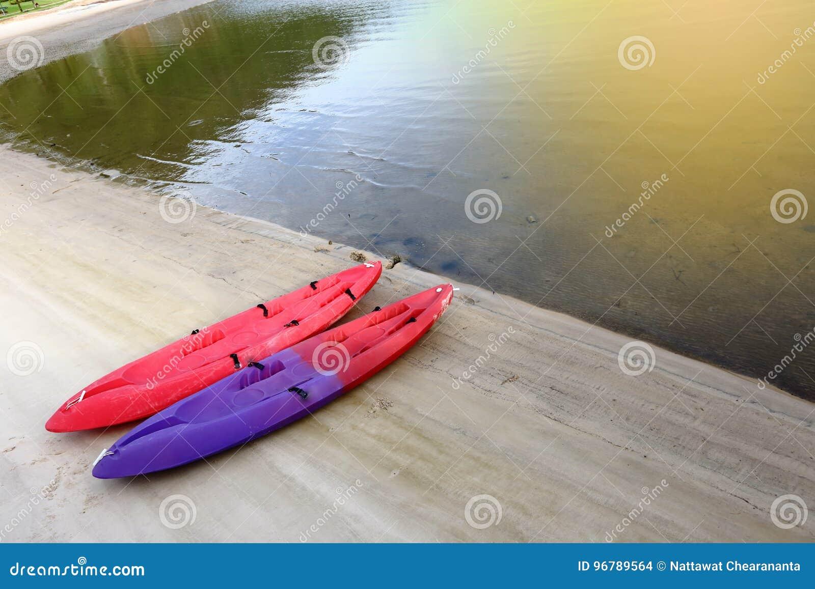 Bote da canoa de dois caiaque em vermelho e em roxo no oceano da praia da areia