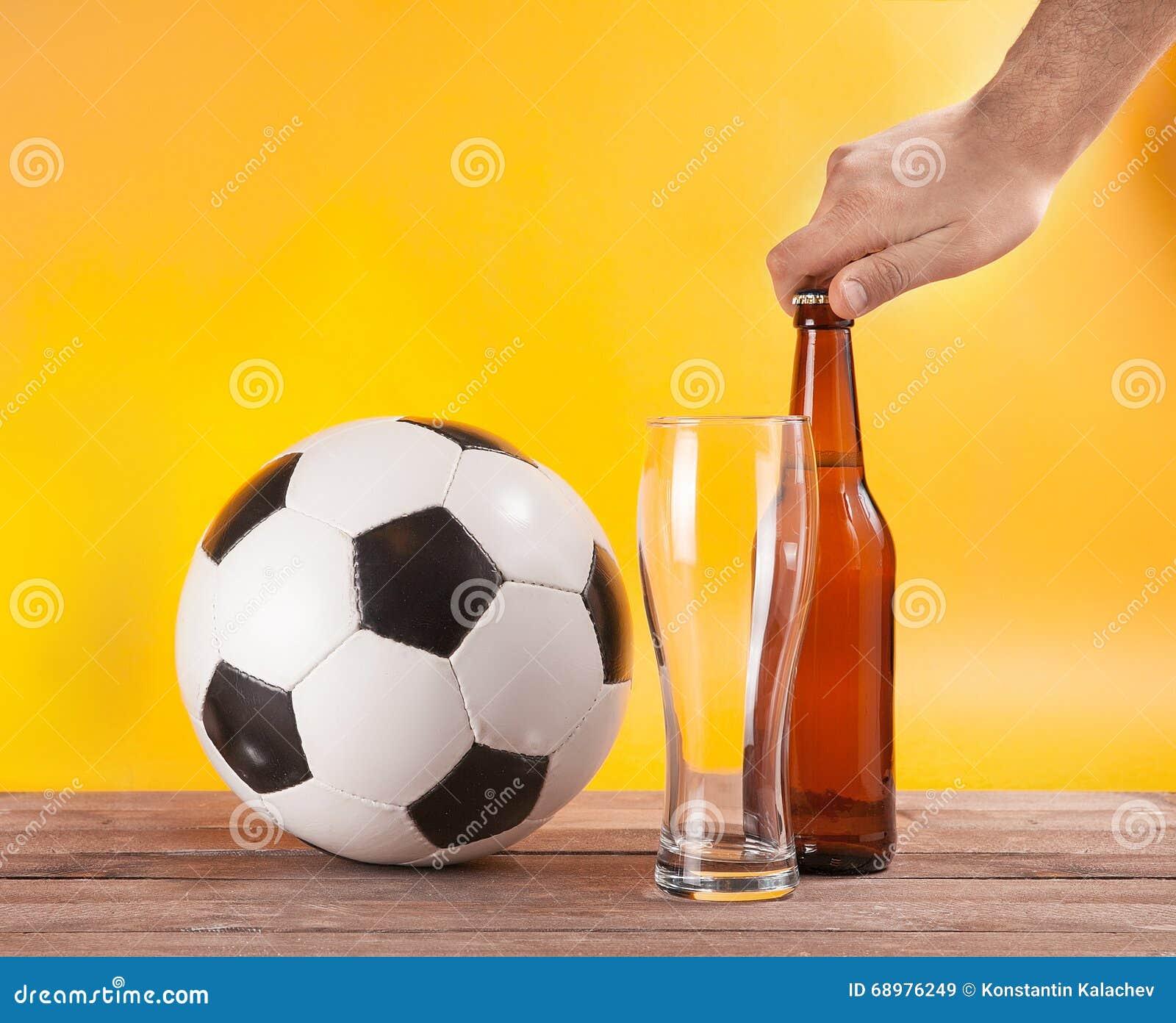Botella abierta de la mano masculina de cerveza cerca del vidrio del balón de fútbol