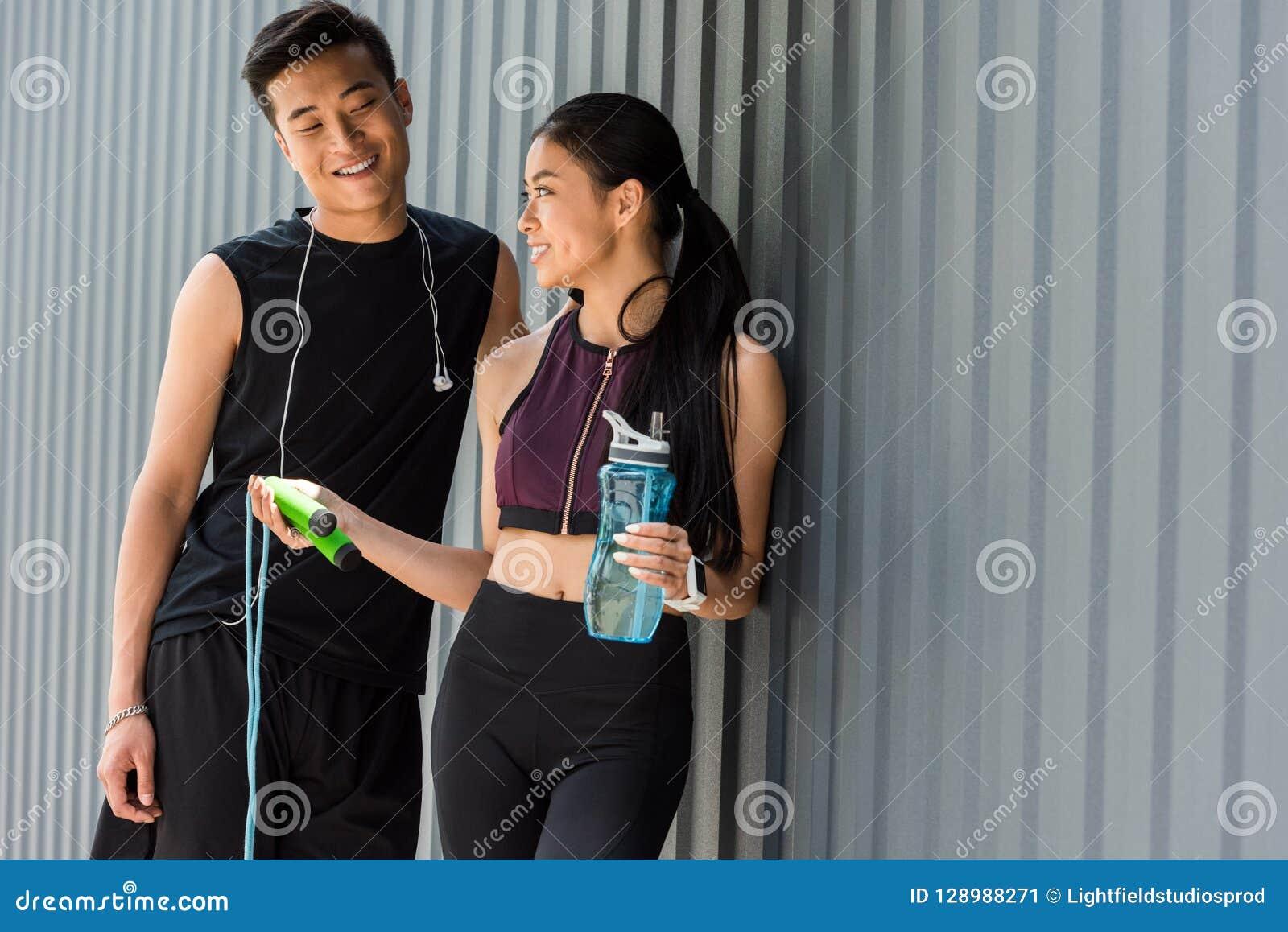 Botella asiática sonriente de la tenencia de la deportista de agua y de dar la comba al deportista joven