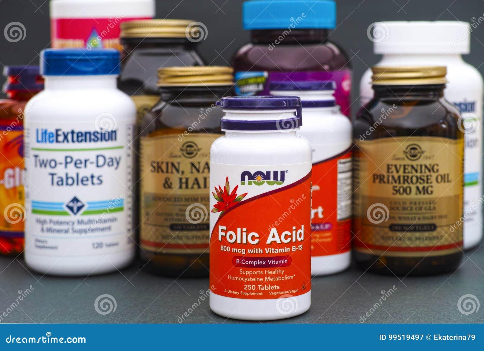 Botella con el ácido fólico ahora y algunas botellas con las vitaminas y