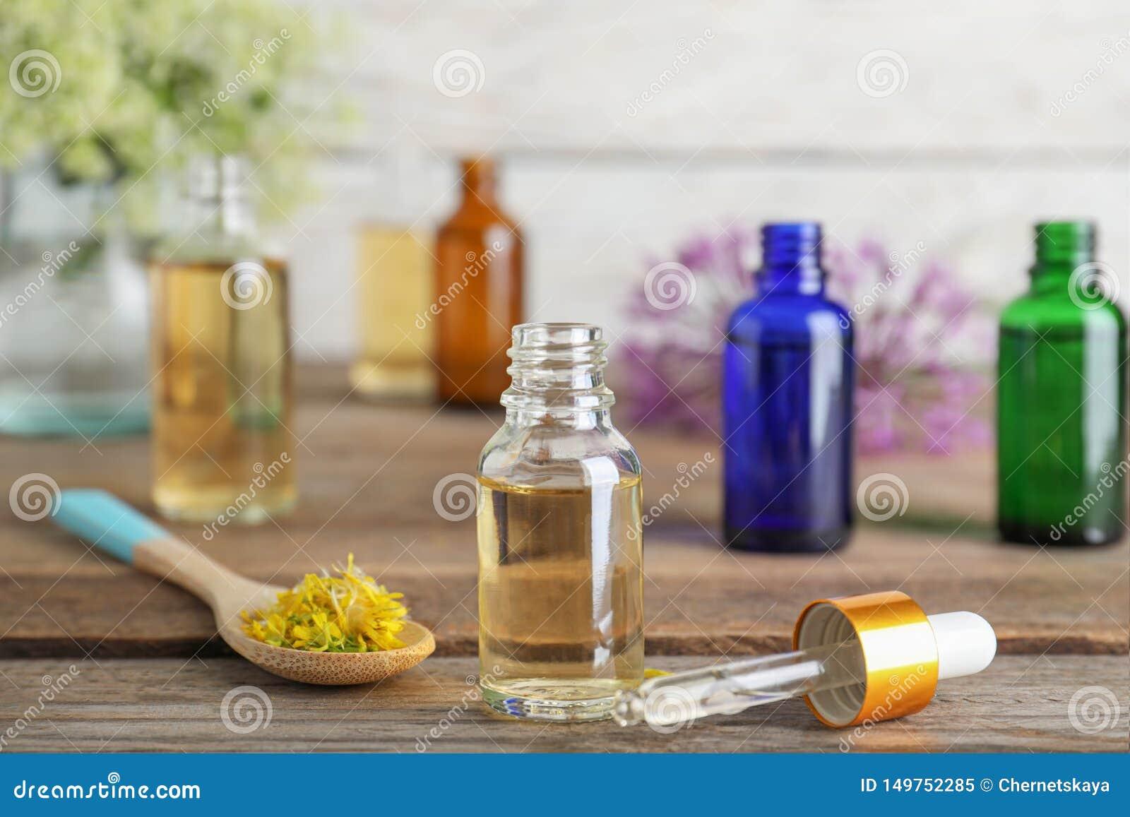 Botella de aceite esencial, de pipeta y de cuchara con las flores en la tabla de madera