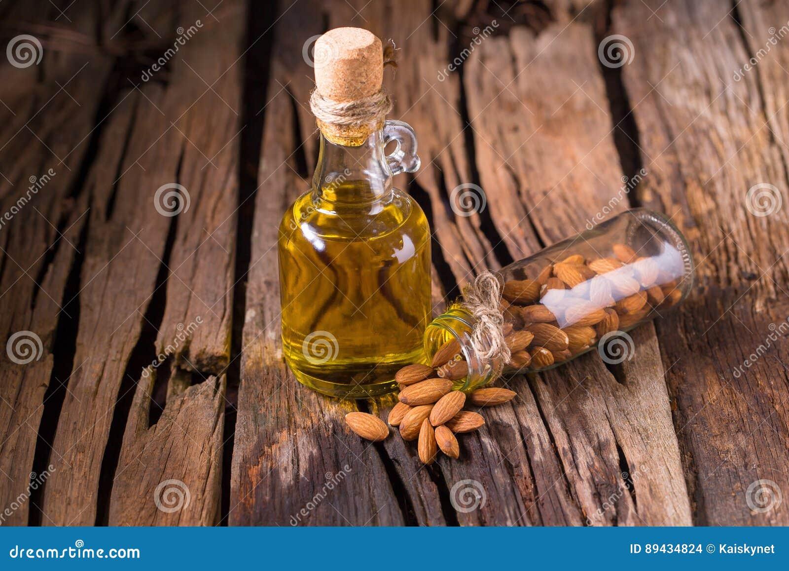 Botella de aceite y de almendras de almendra en viejo fondo de madera de la tabla