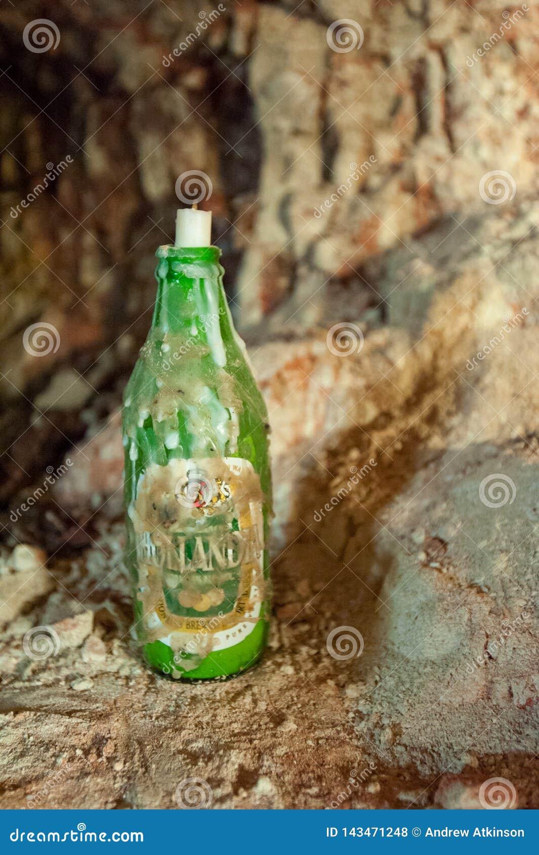 Botella de cerveza vieja con una vela en el goteo superior con la cera