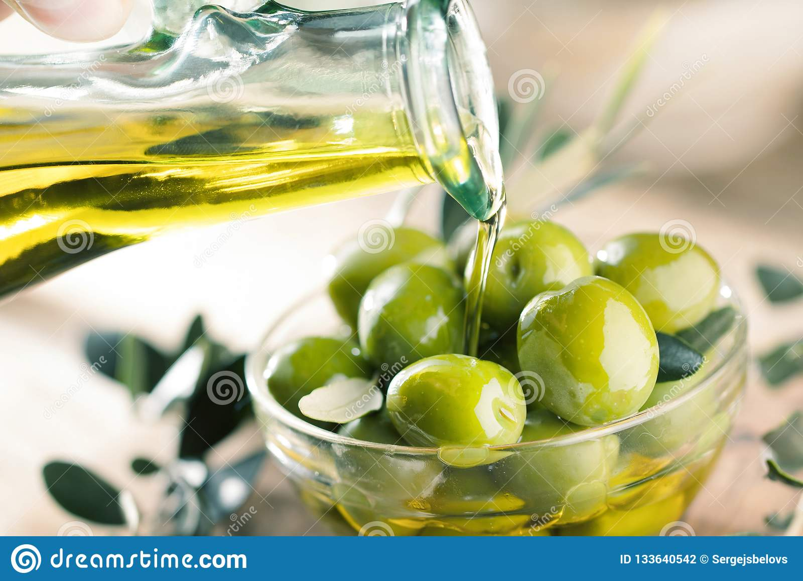 Botella de cristal de aceite de oliva virginal superior y de algunas aceitunas con el le