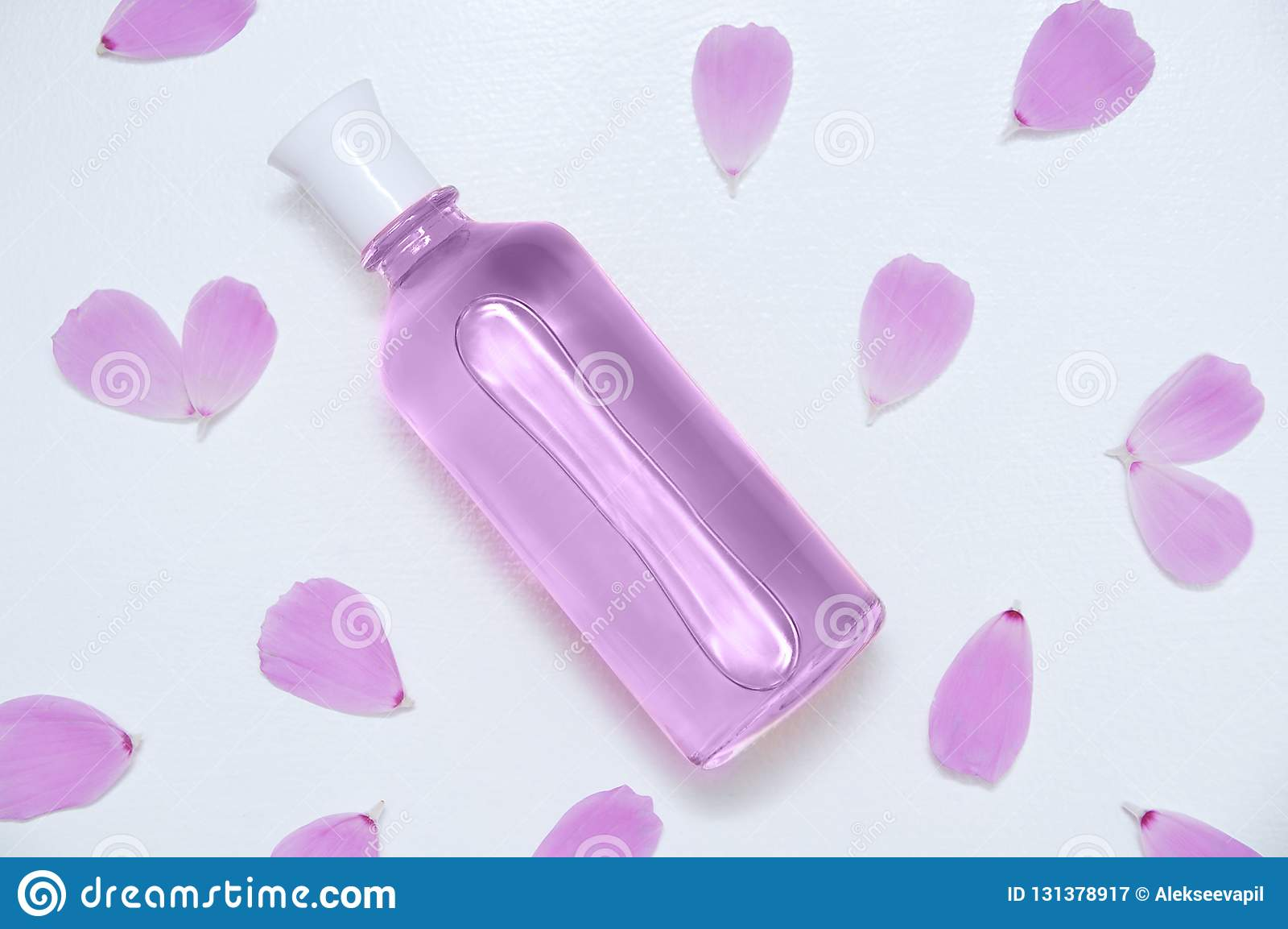 Botella de cristal con los pétalos del perfume y de la flor