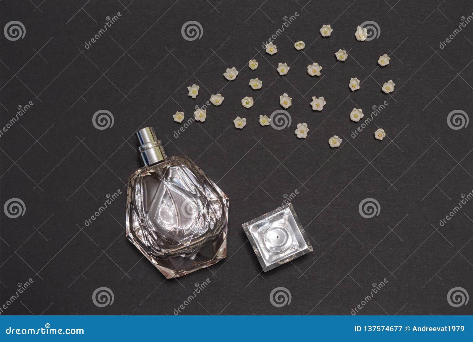 Botella de perfume y de lirios de los brotes de flor del valle en fondo negro Perfumería, fragancia, concepto cosmético Primavera