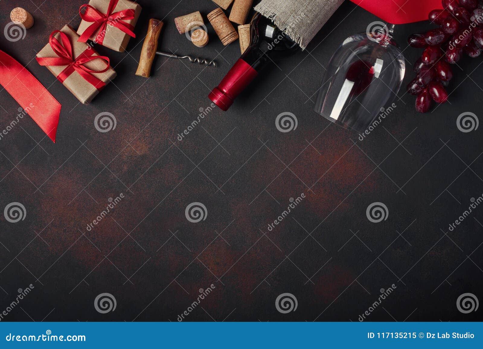 Botella de vino, caja de regalo, uvas rojas, sacacorchos y corchos, en el ru