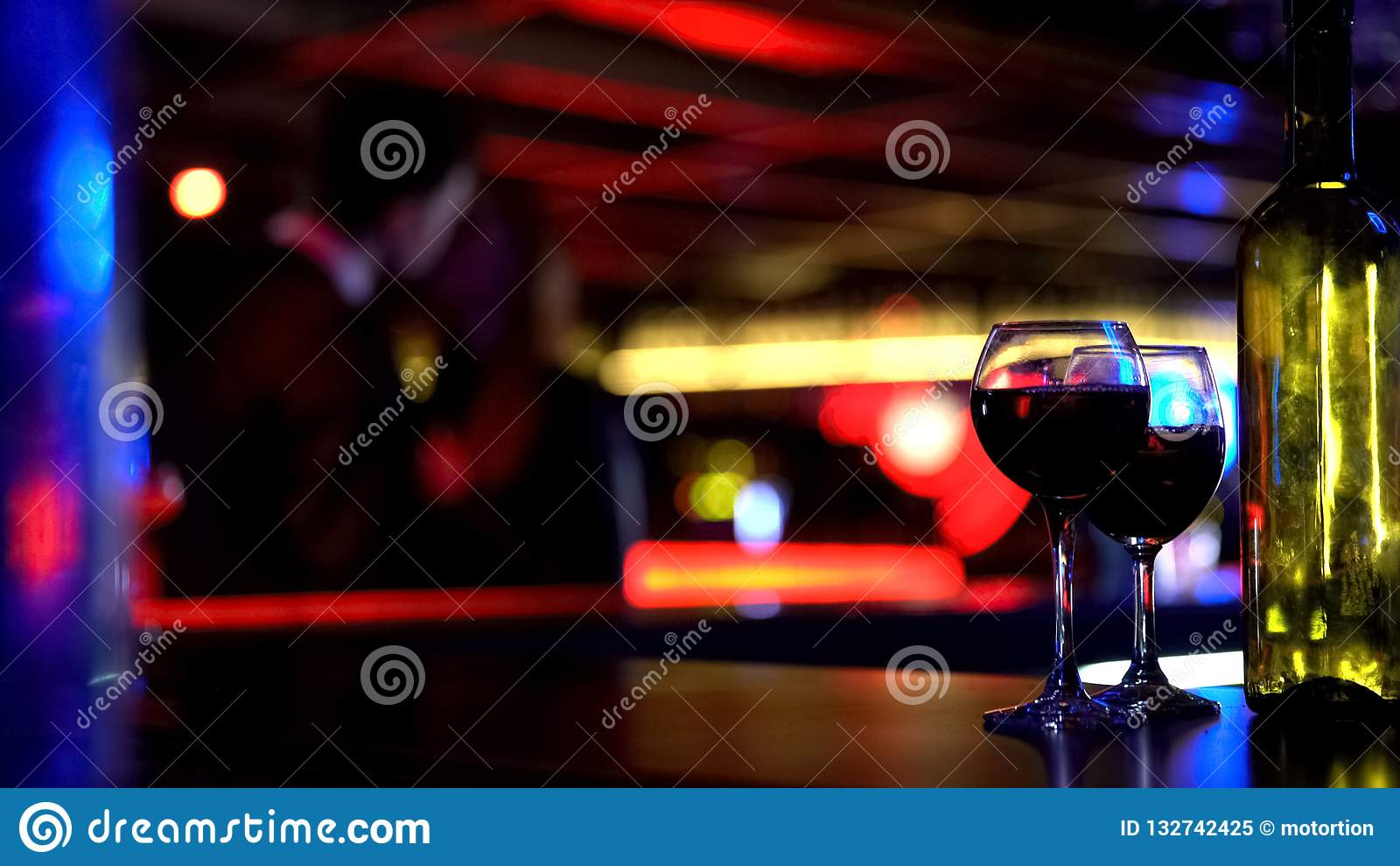 Botella de vino con dos vidrios, besando pares jovenes en fondo borroso