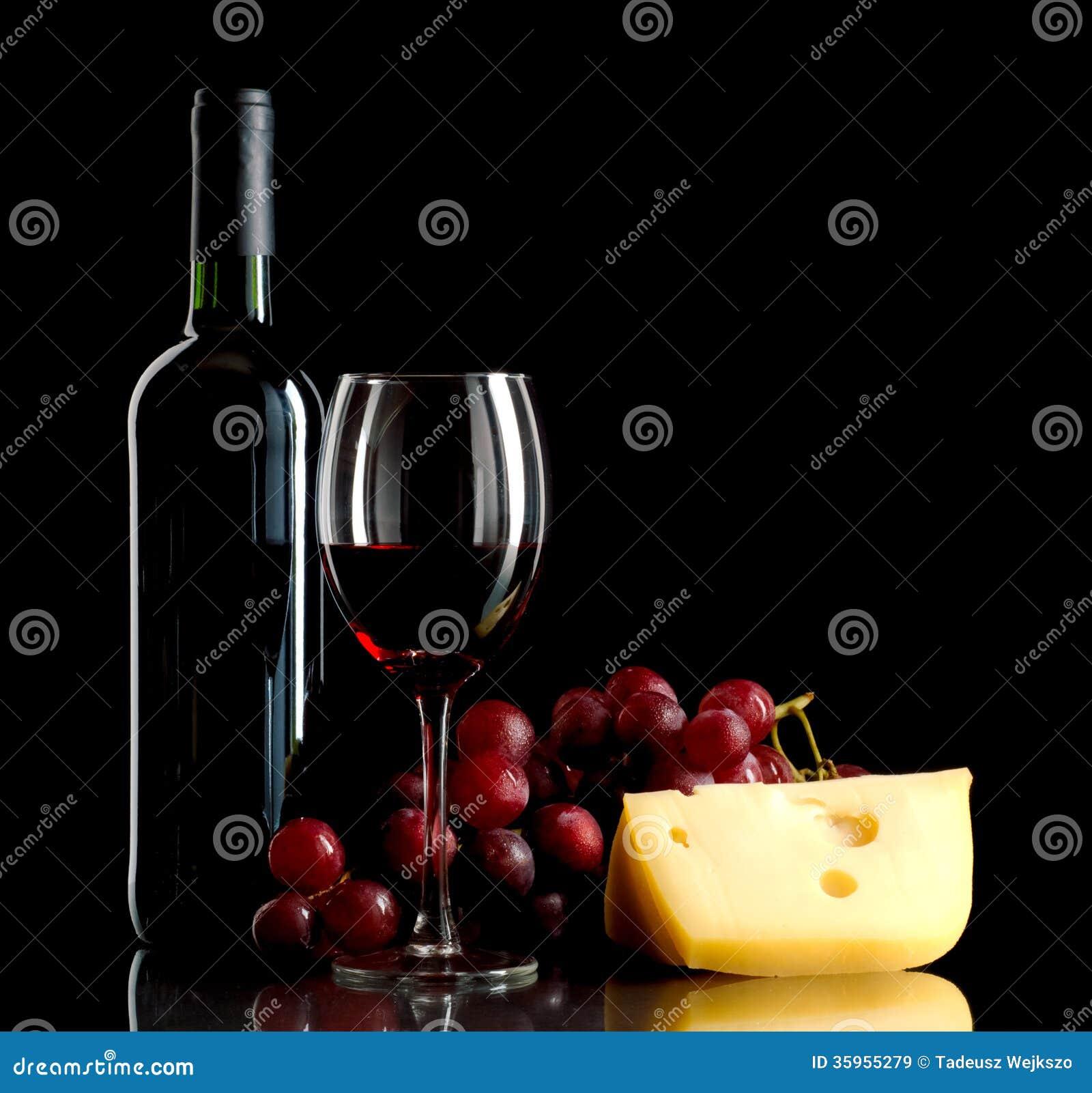 Botella de vino, un manojo de uvas rojas y un pedazo de queso