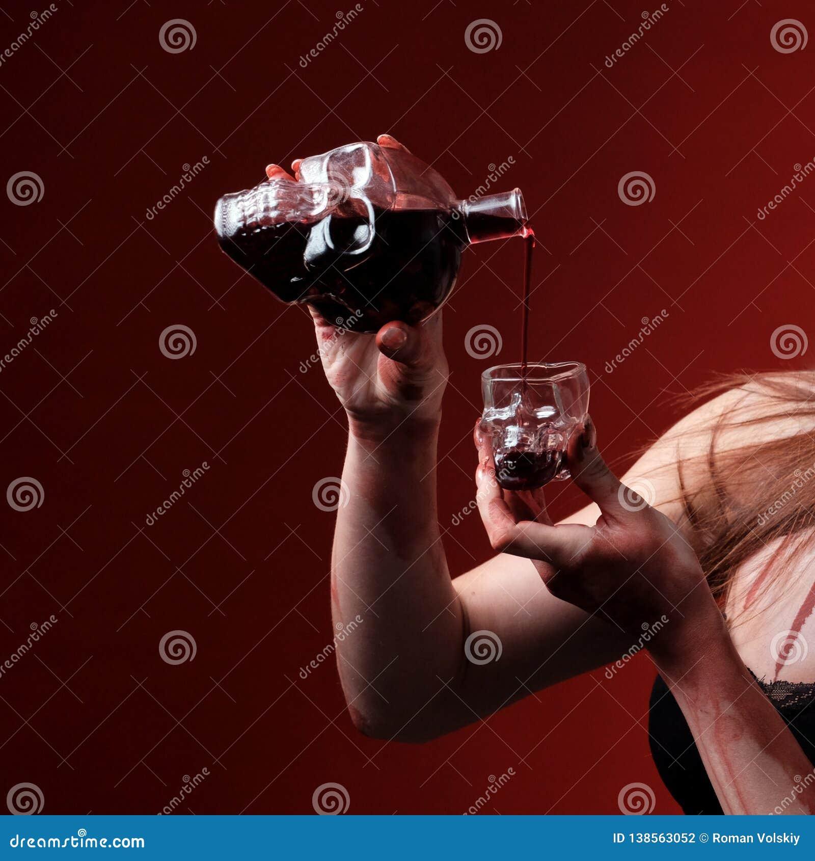 Botella y vidrio bajo la forma de cráneo Las manos femeninas vierten el vino o la sangre Fondo rojo Concepto de la celebración de