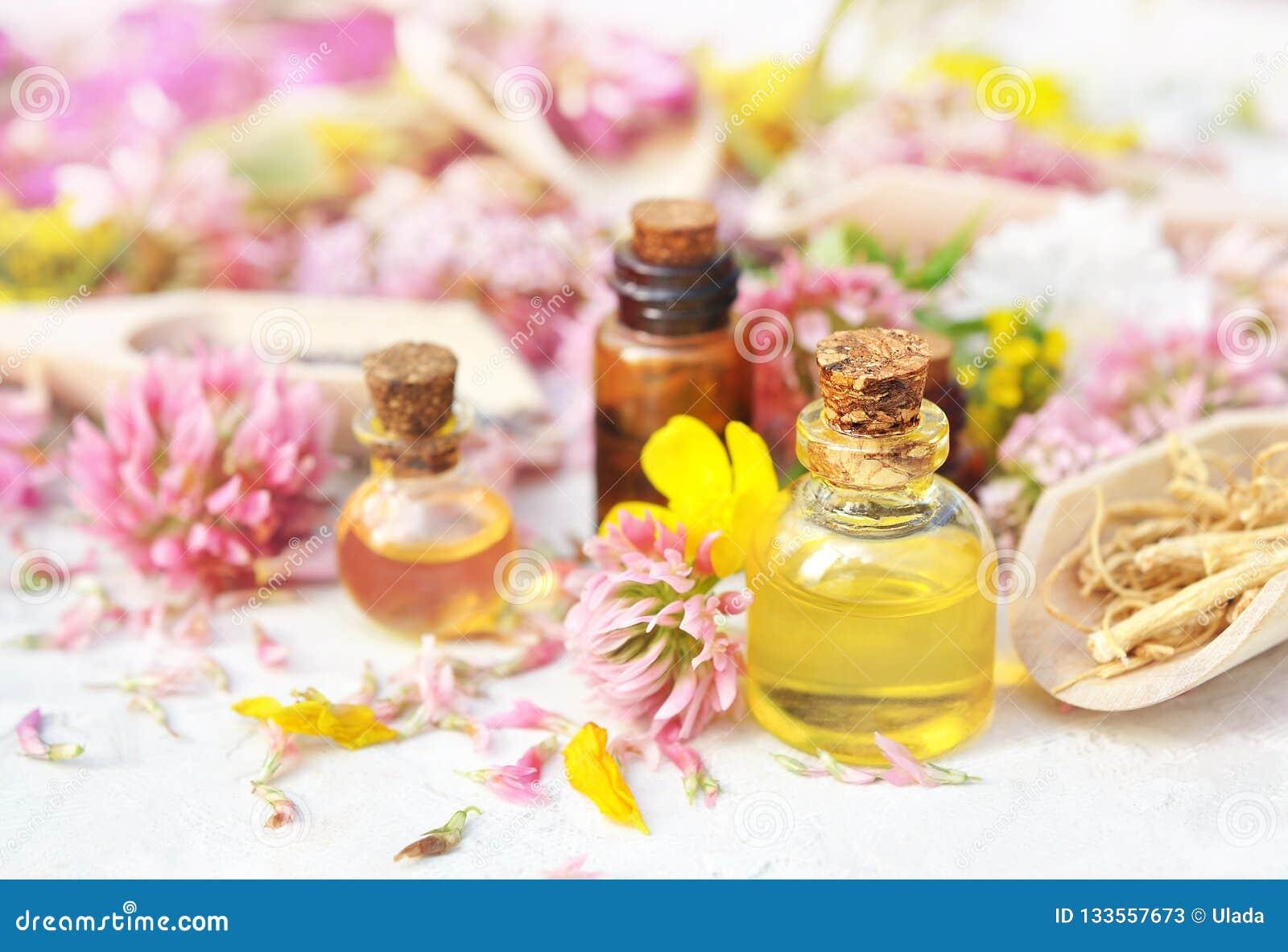 Botellas de aceite esencial en fondo medicinal de las flores y de las hierbas