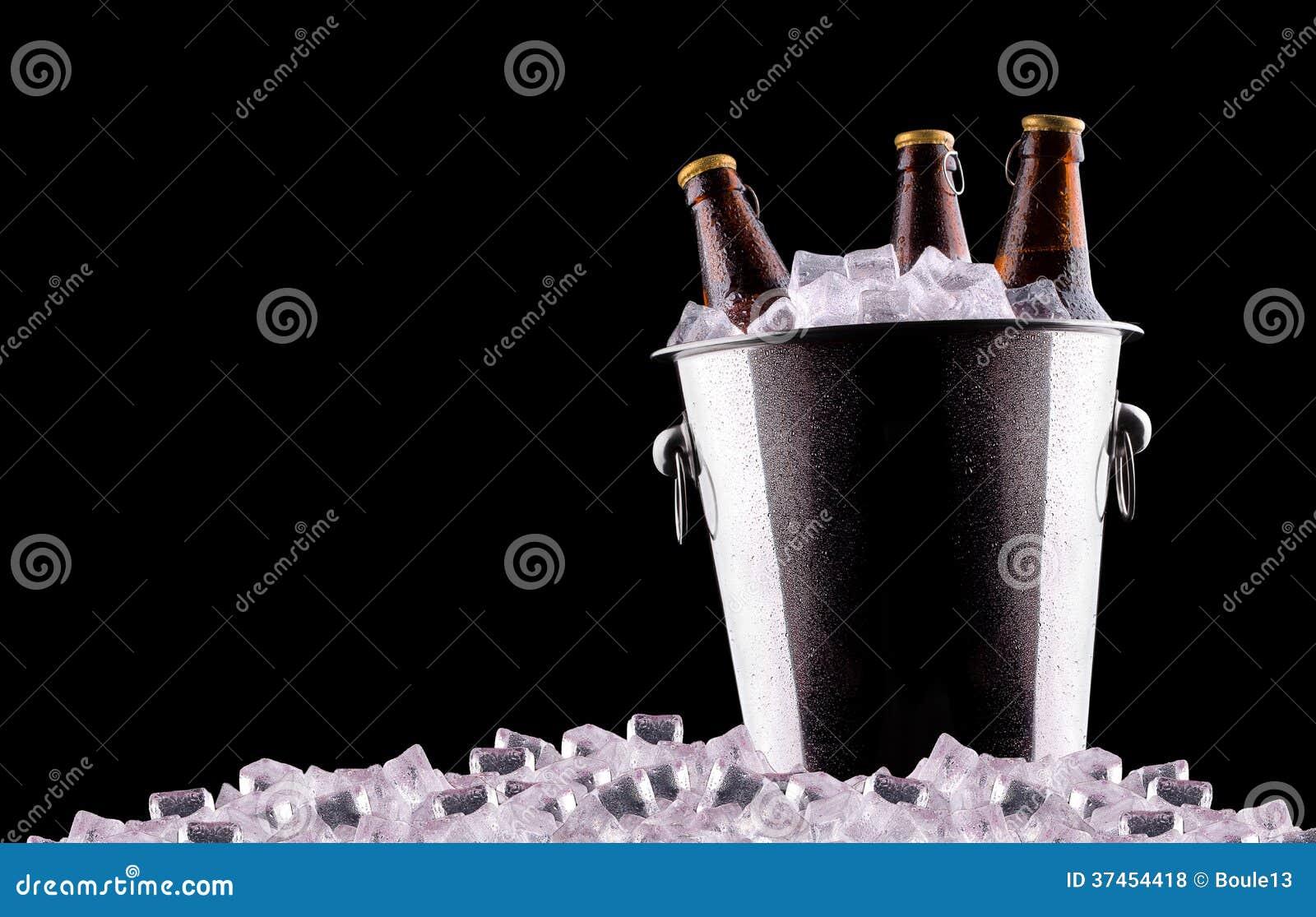 Botellas de cerveza en cubo de hielo