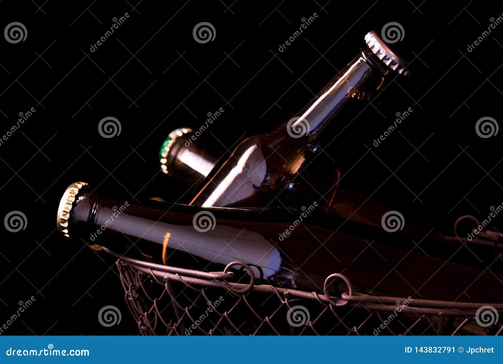 Botellas de cerveza en un claroscuro negro del fondo en una cesta vieja de la malla metálica