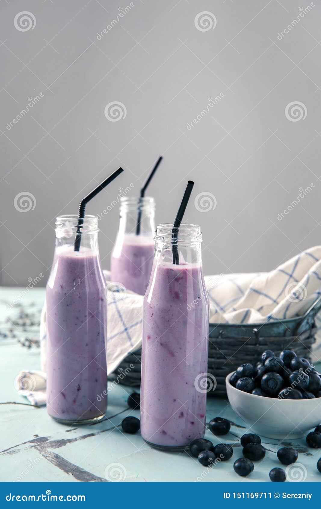 Botellas de cristal con el smoothie sabroso del arándano en la tabla