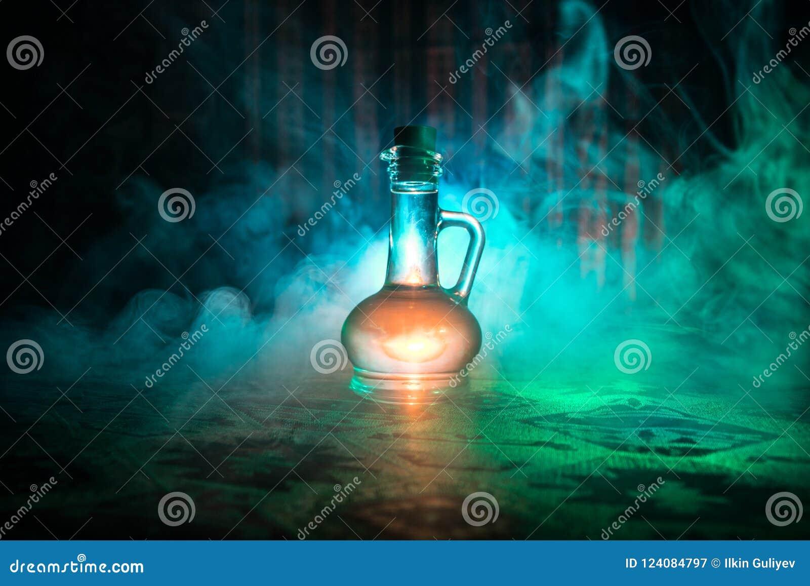 Botellas de cristal de la antigüedad y del vintage en fondo de niebla oscuro con la luz Veneno o concepto del líquido de la magia