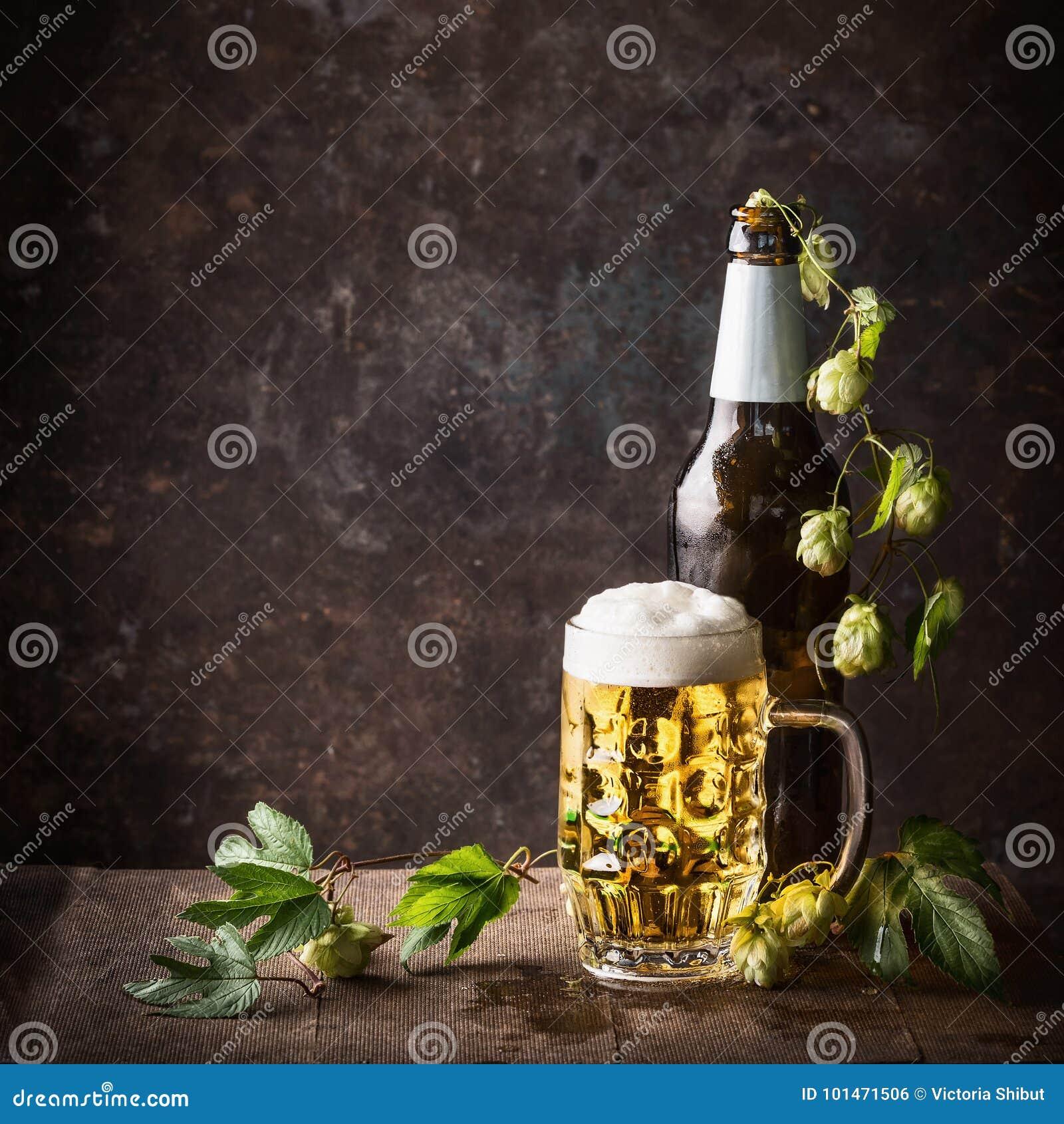 Botellas de cristal y taza de cerveza con el casquillo de la espuma y los saltos en la tabla en el fondo rústico oscuro, vista de