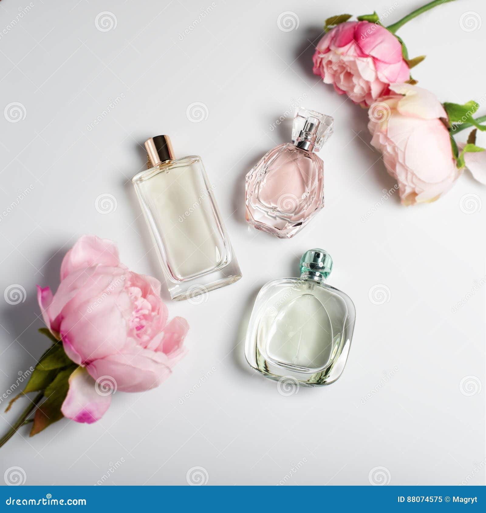 Botellas de perfume con las flores en fondo ligero Perfumería, cosméticos, colección de la fragancia Endecha plana