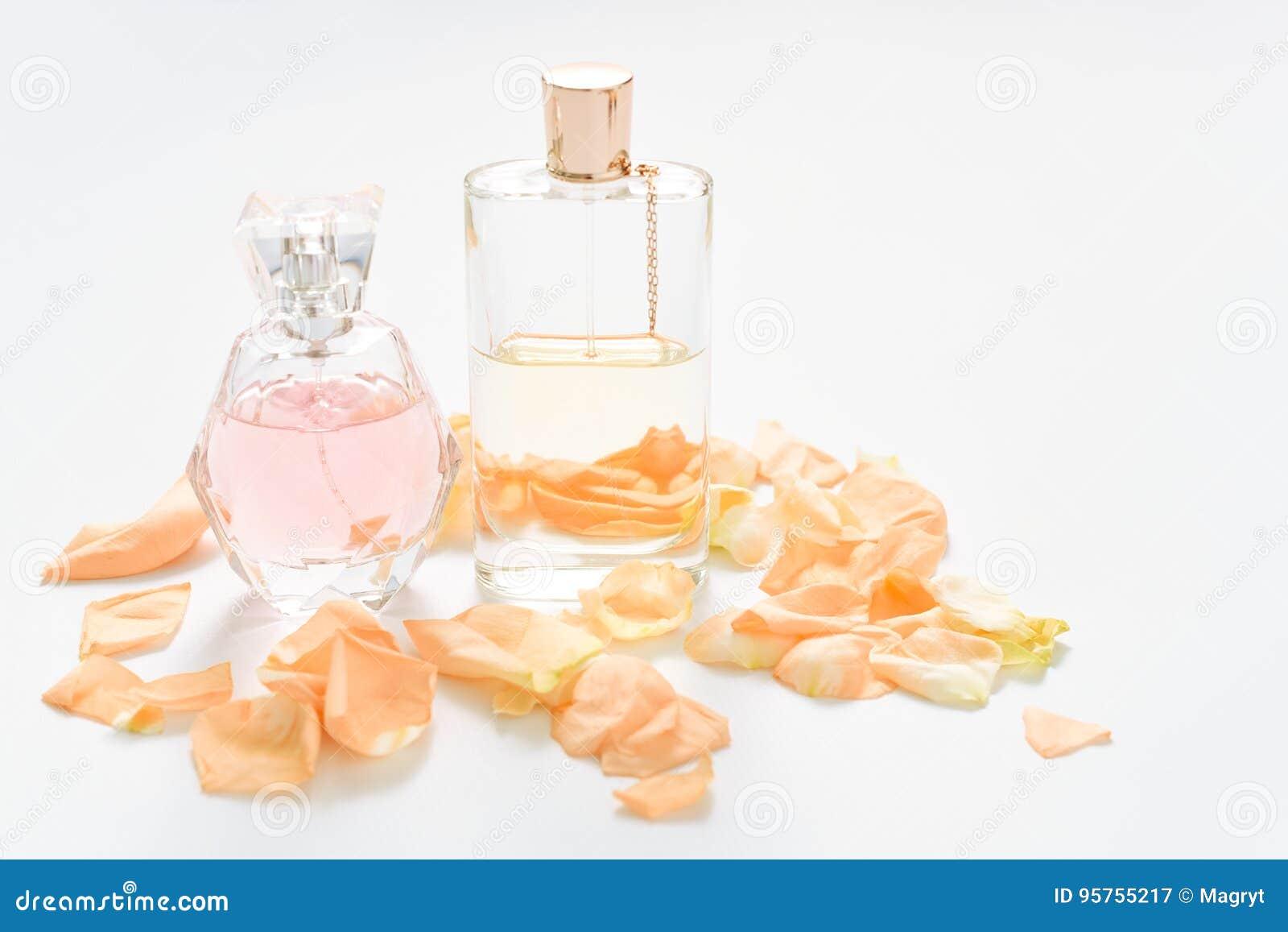 Botellas de perfume con los pétalos de la flor en fondo ligero Perfumería, colección de la fragancia Accesorios de las mujeres