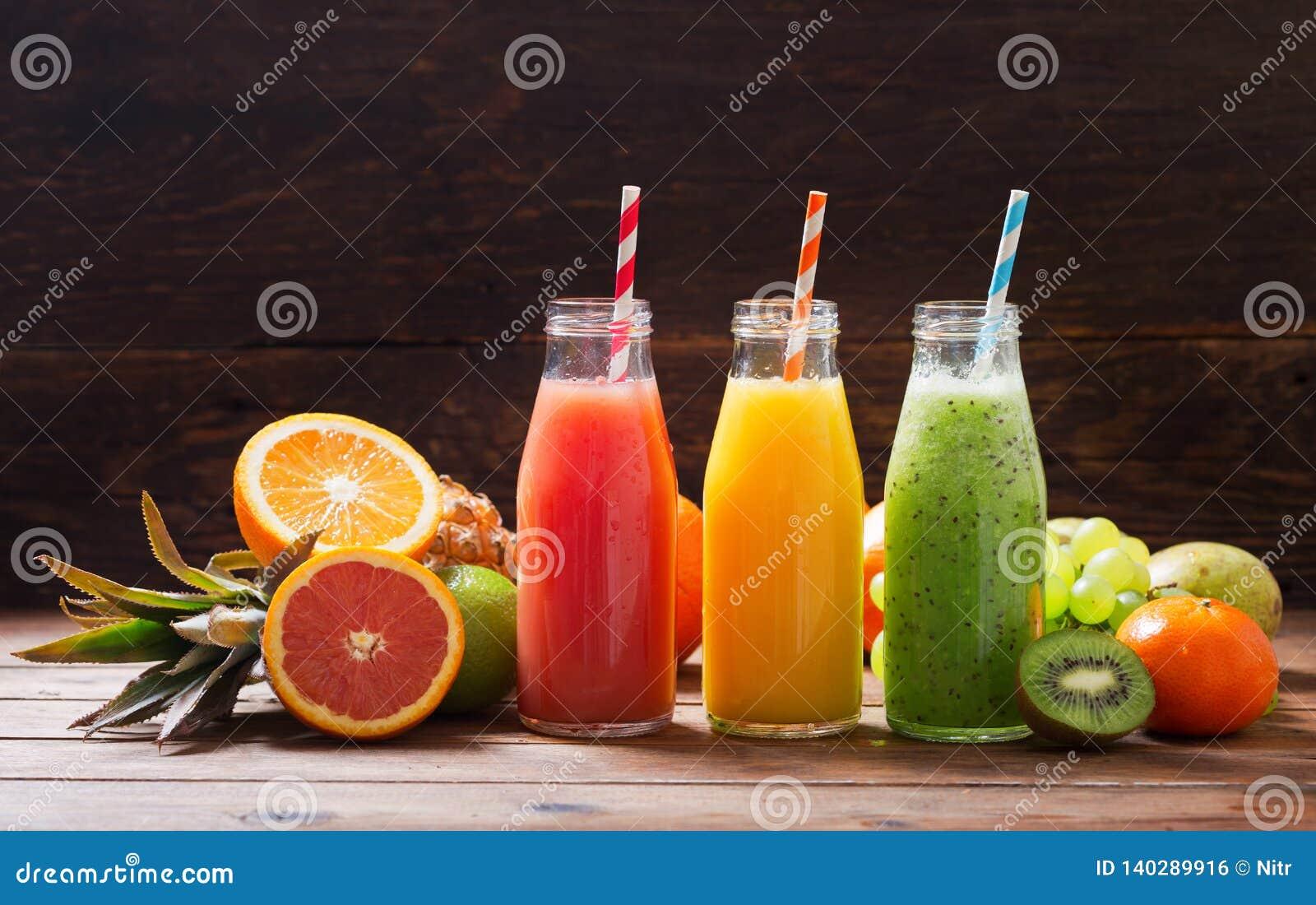 Botellas de zumo de fruta y de smoothie con las frutas frescas