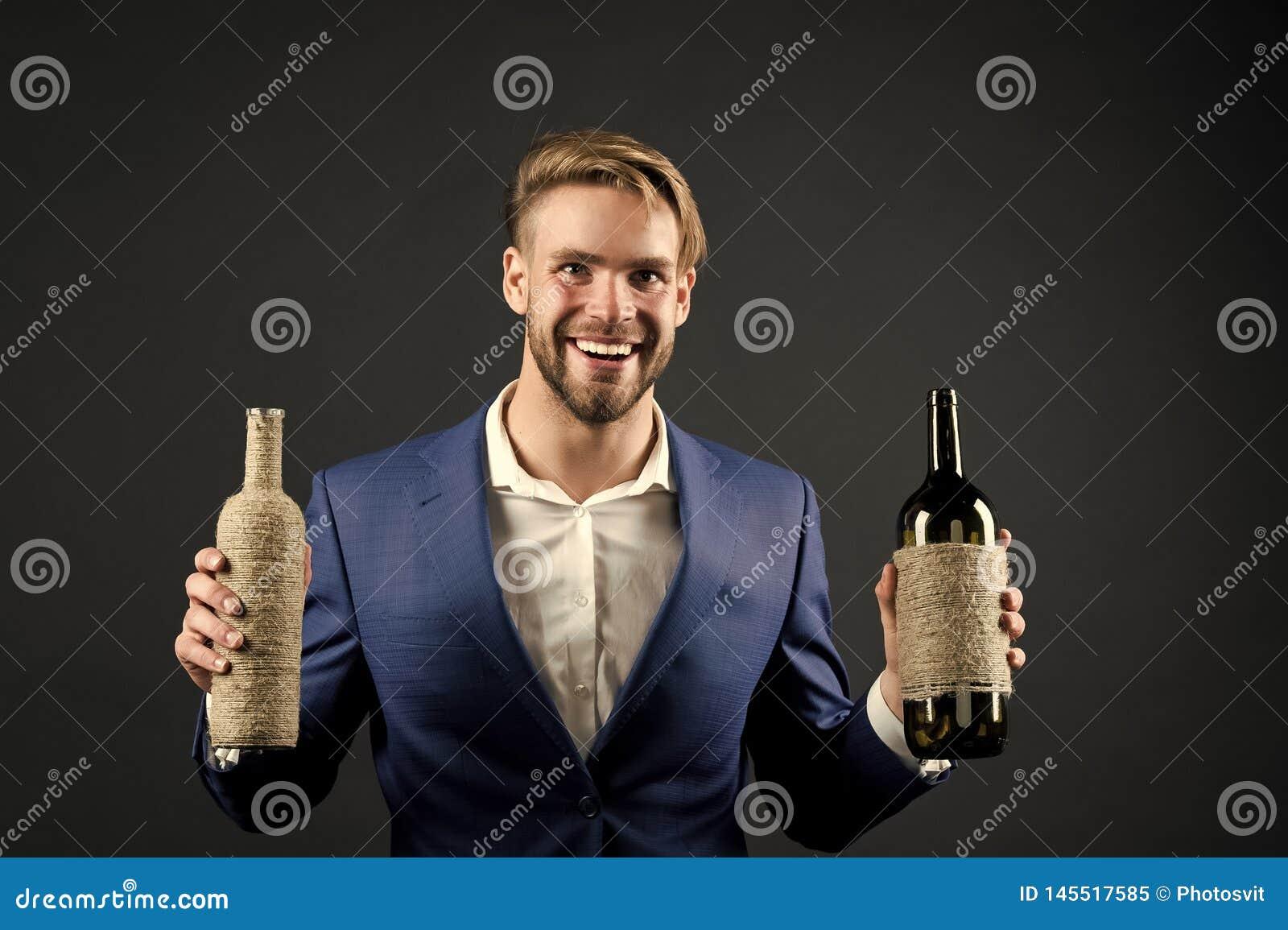 Botellas del control dos del Sommelier de vino Concepto profesional del degustation del vino Sirva el traje formal con las botell