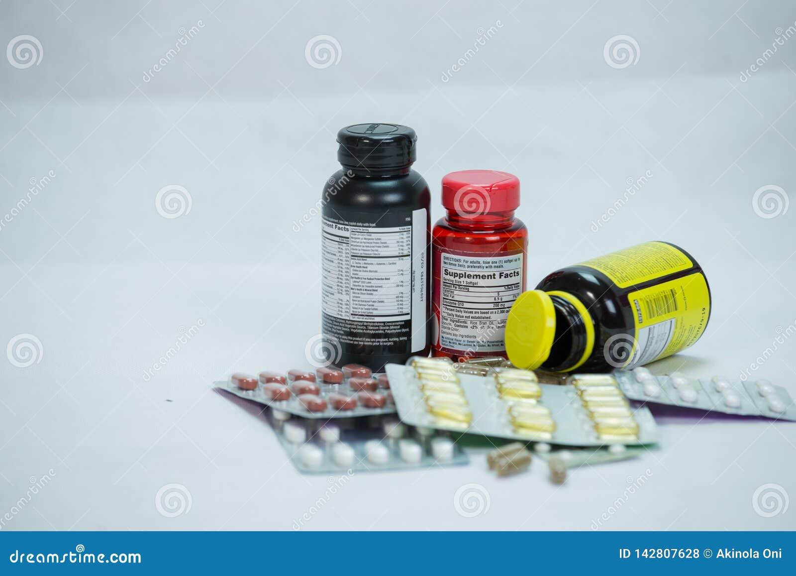 Botellas múltiples de la prescripción con las tabletas en el fondo blanco