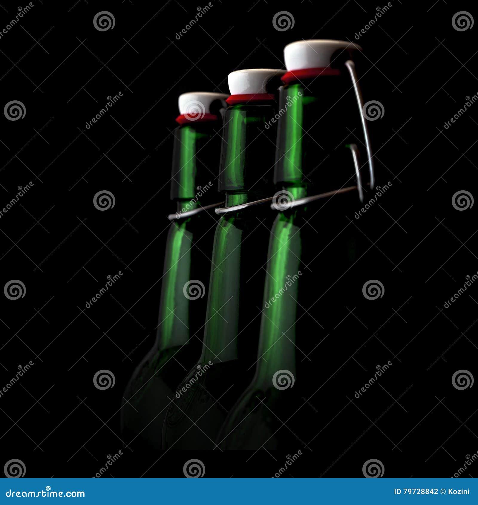 Botellas viejas del verde del fasion en un fondo negro