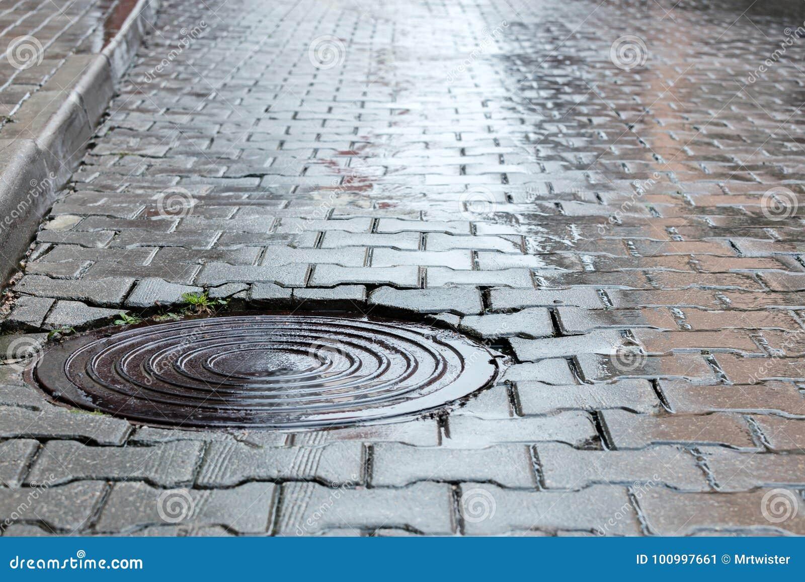 Botola d acciaio rotonda della fogna sulla strada bagnata del ciottolo