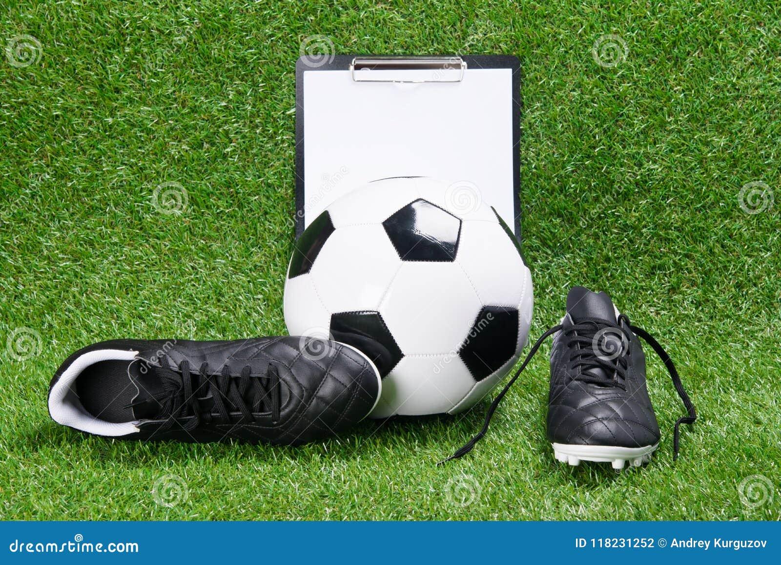 Bottes, boule du football et comprimé pour écrire, dans la perspective de l herbe