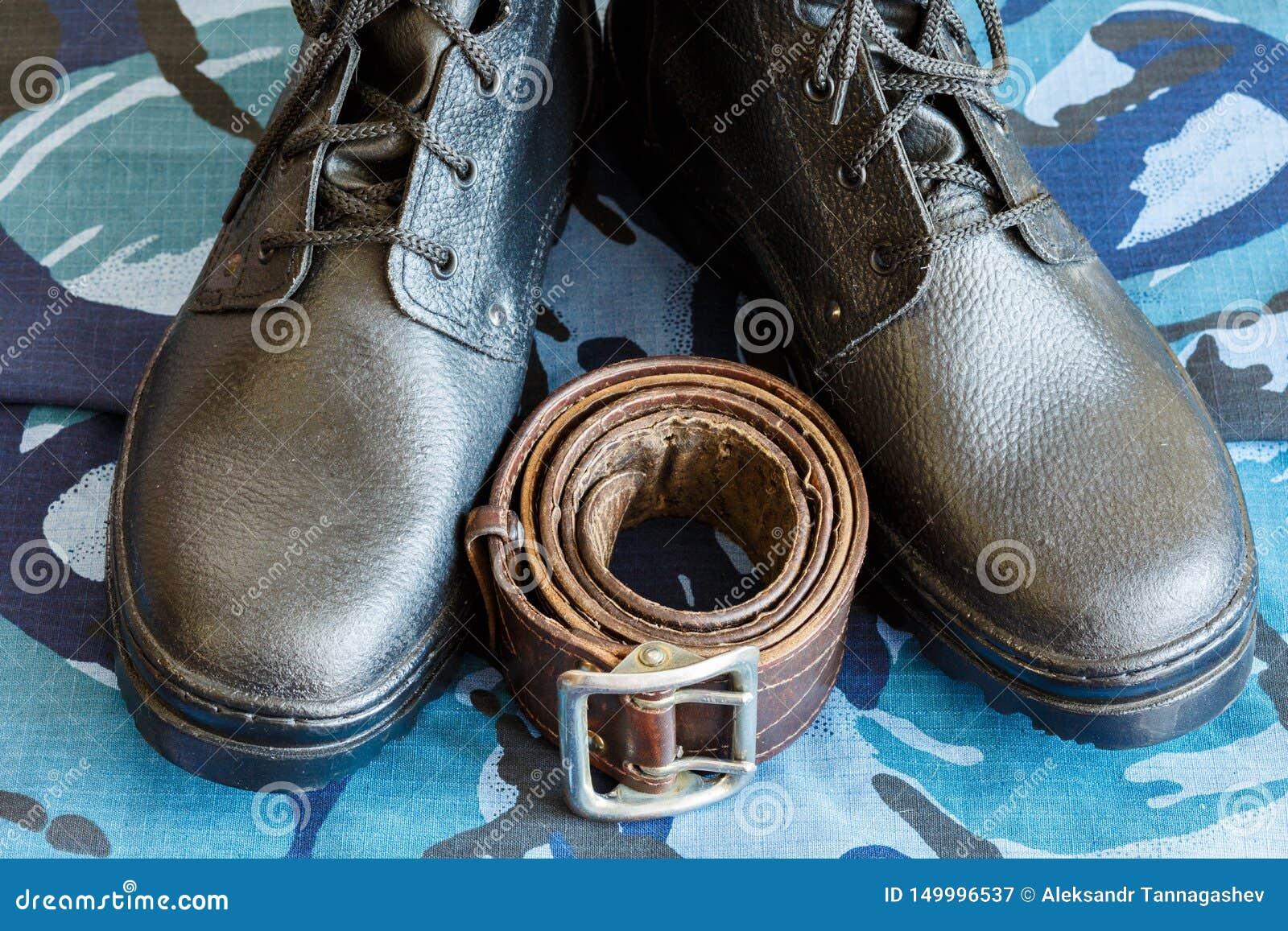 Bottes d armée et ceinture d armée sur le tissu bleu de camouflage De façon générale pour le soldat
