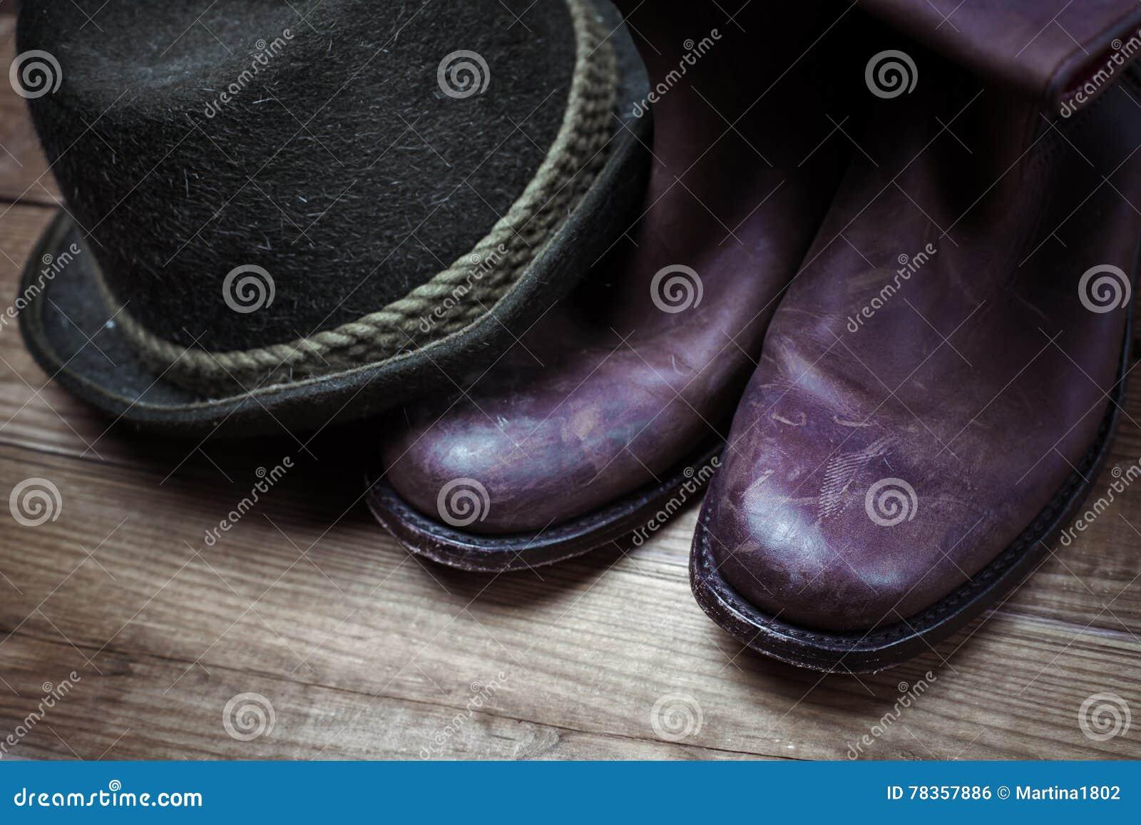 Bottes de cowboy et chapeau bruns sales et utilisés