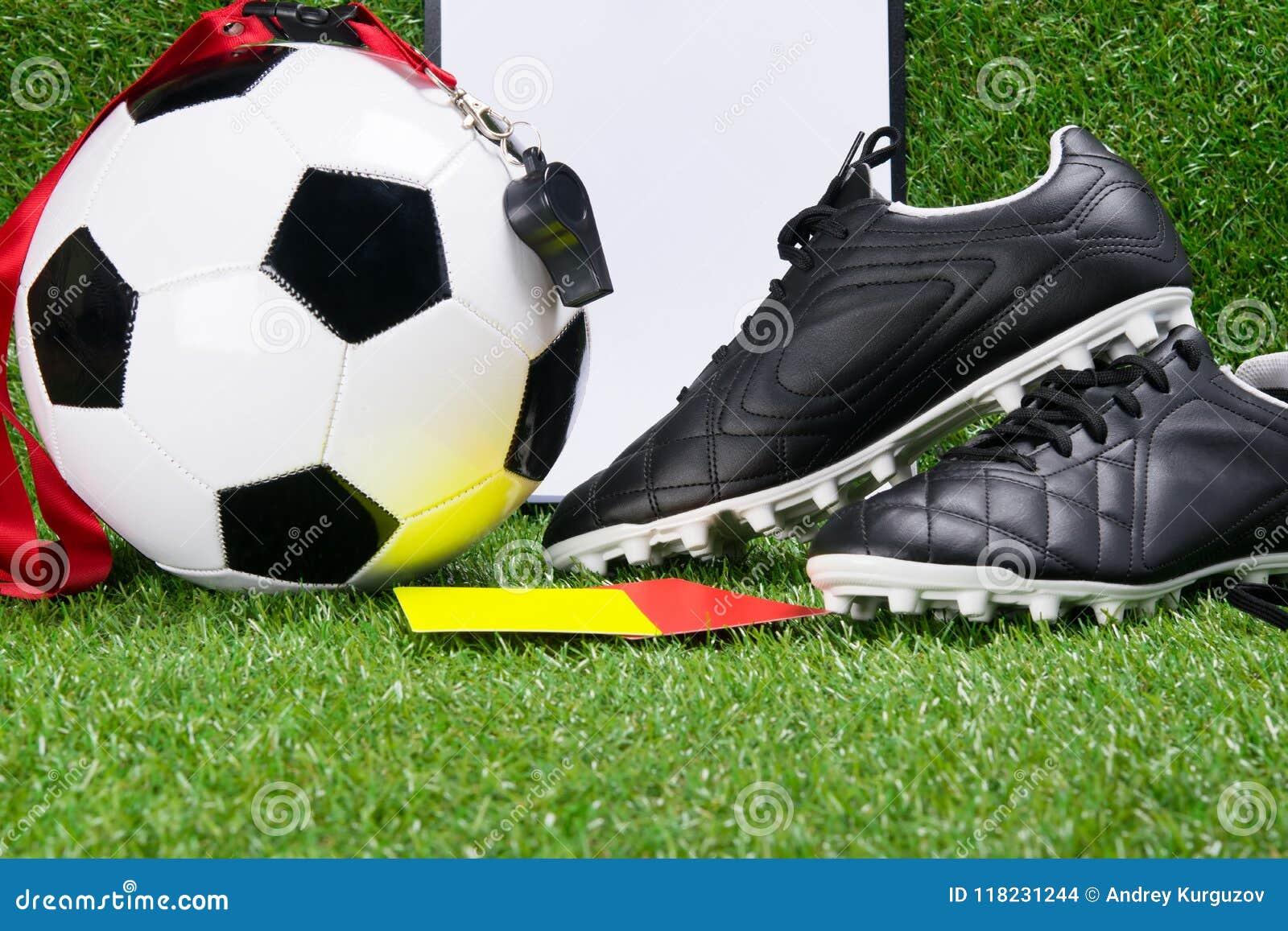 Bottes, une boule du football, un bloc - notes, un sifflement et cartes de pénalité pour un juge, dans la perspective d herbe