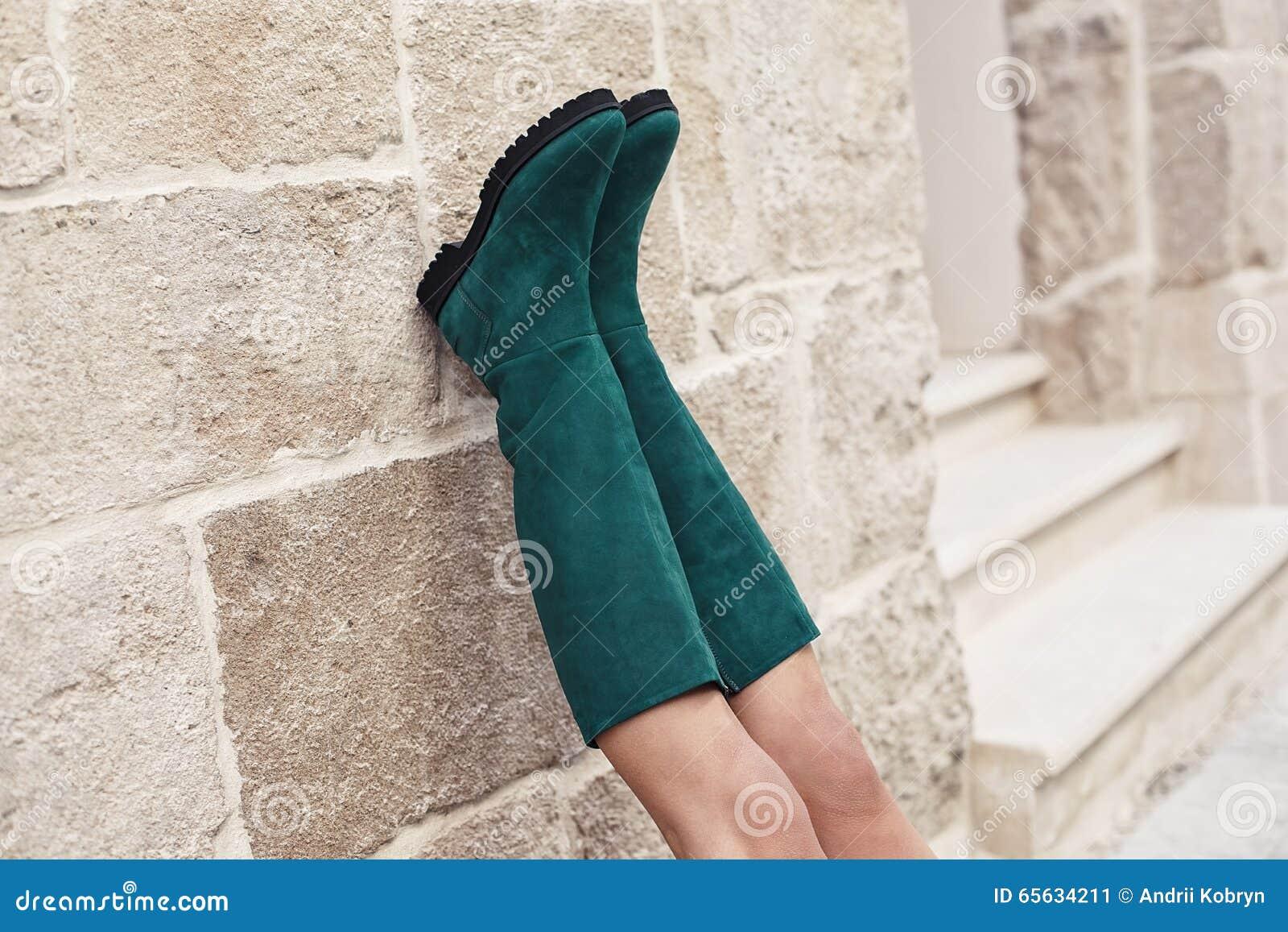 Bottes vertes sur les pieds de la femme se penchant sur le mur en pierre