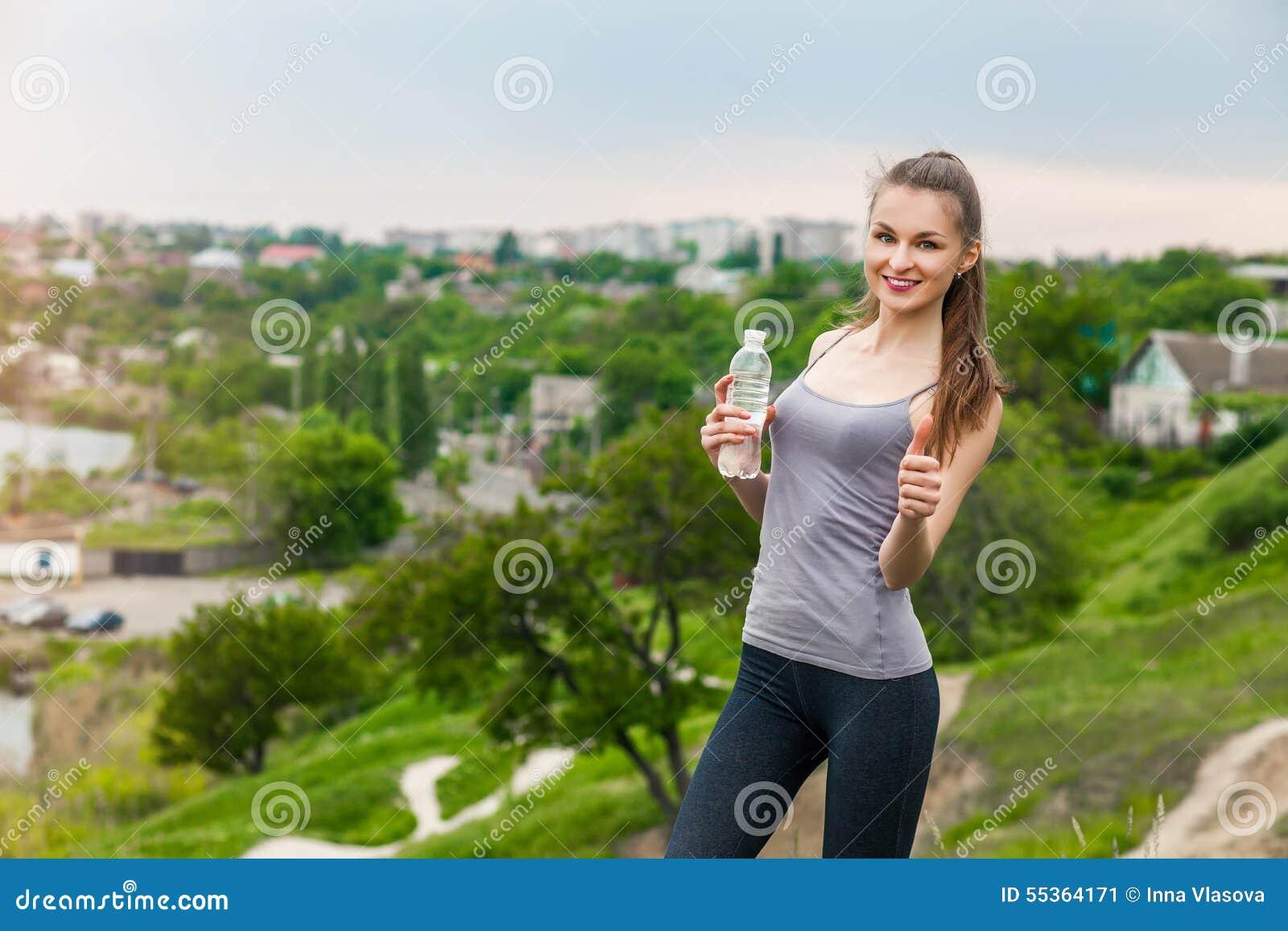 Bottiglia assetata della tenuta della ragazza di forma fisica di acqua