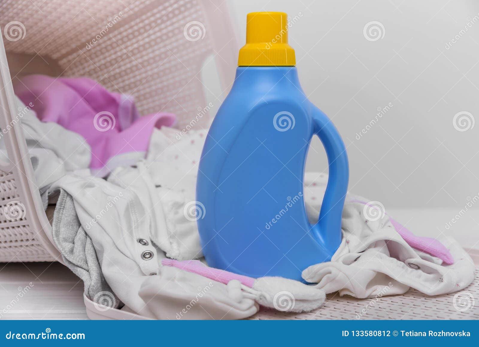Bottiglia del detersivo di lavanderia nel canestro con i vestiti sporchi del bambino