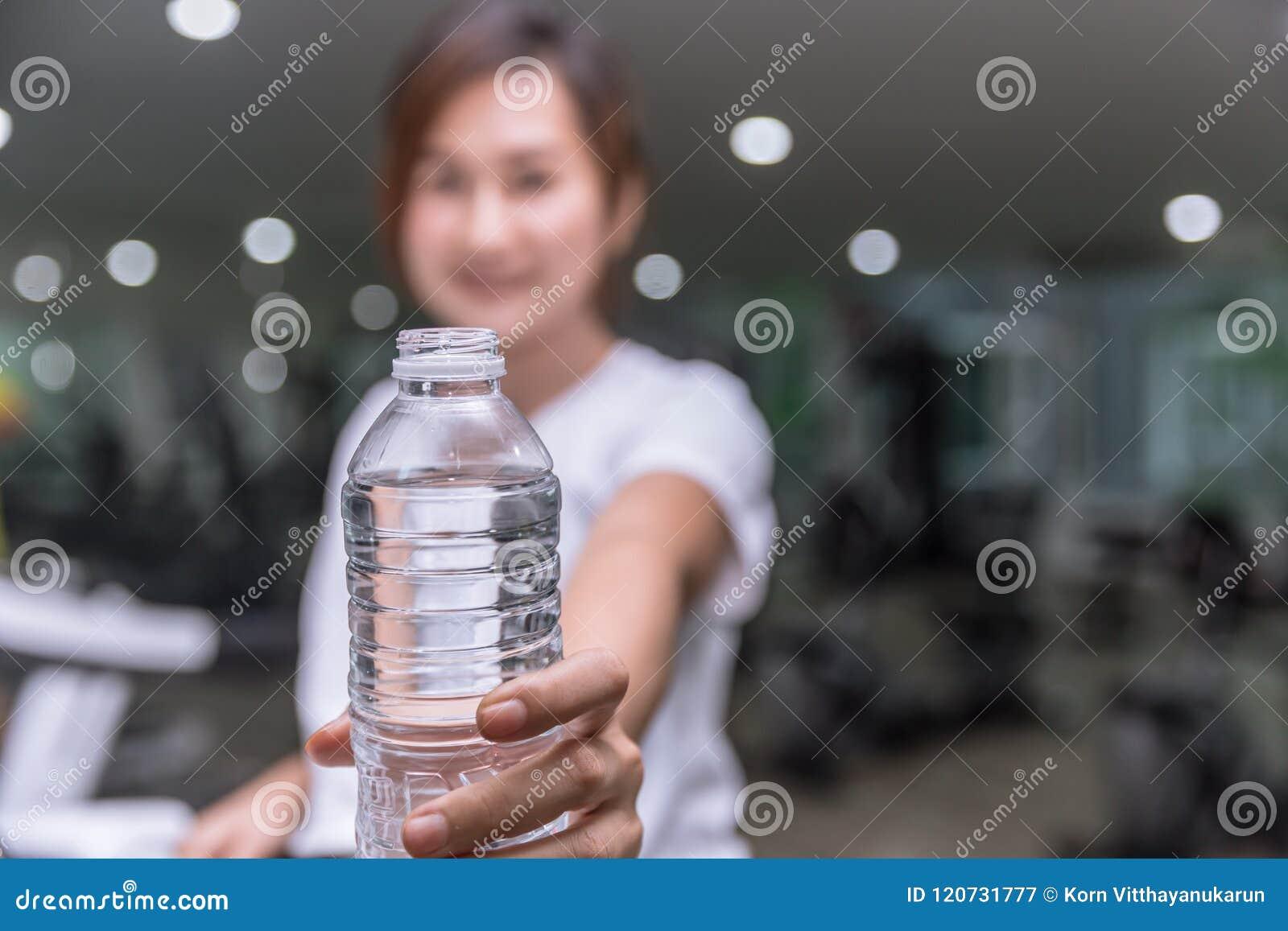 Bottiglia di acqua sana di elasticità della tenuta della mano di sorriso della ragazza di forma fisica di acqua potabile